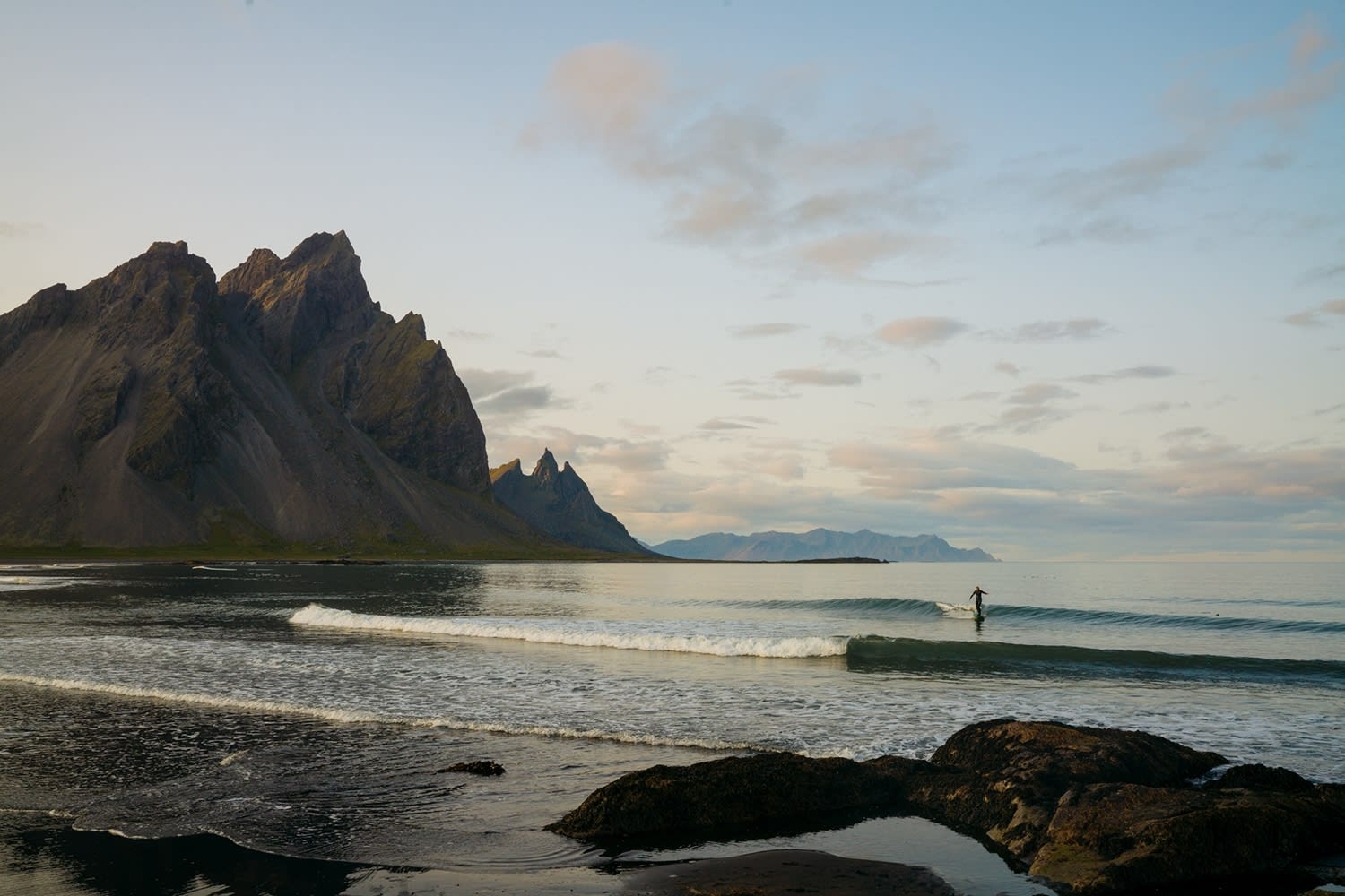 Vestrahorn in East Iceland pictured on a calm, blue sky, day where a person can be seen wading through the water towards the camera