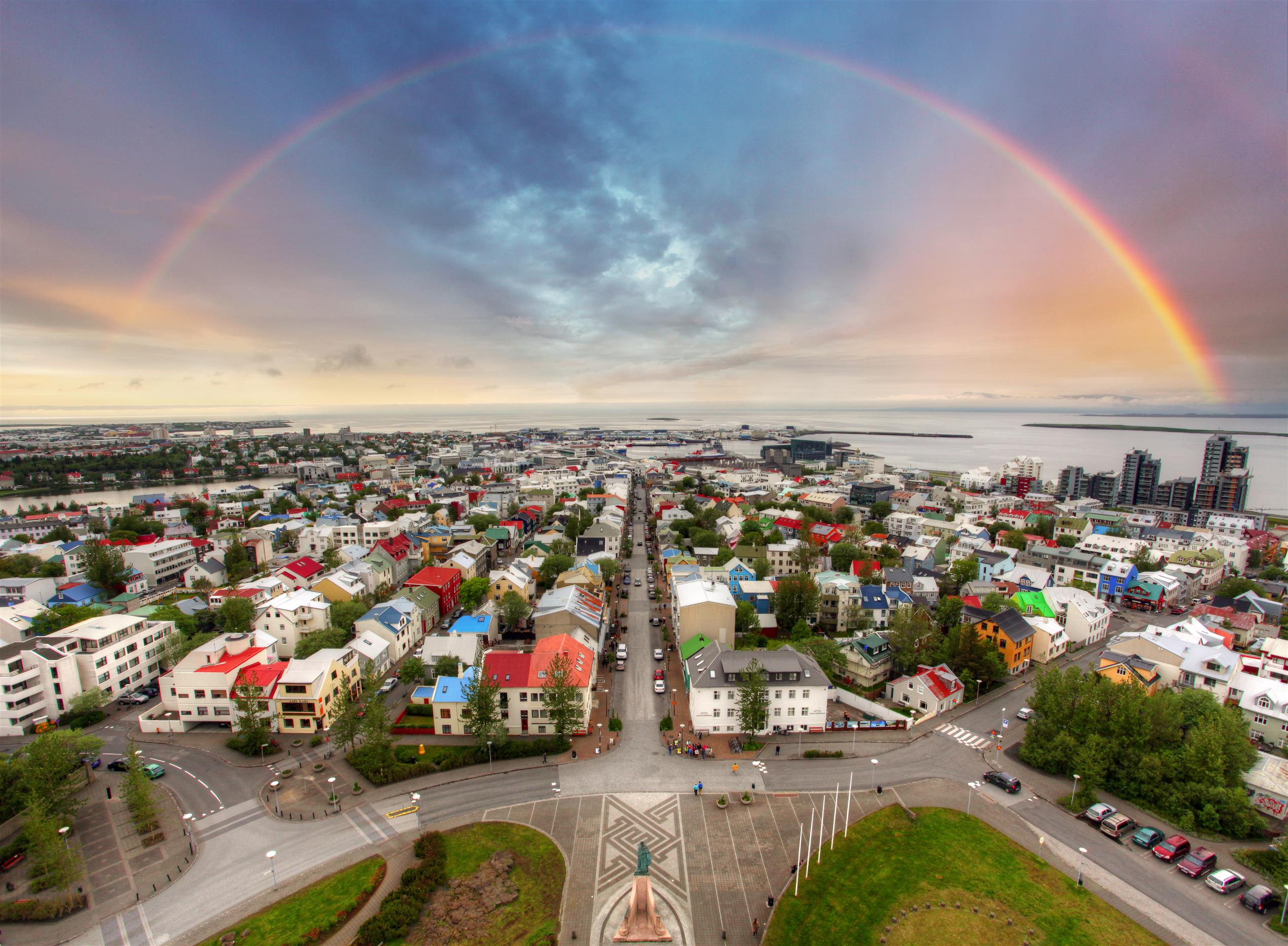 An overhead view of Reykjavik city on a bright day with a rainbow overhead that circles across the city