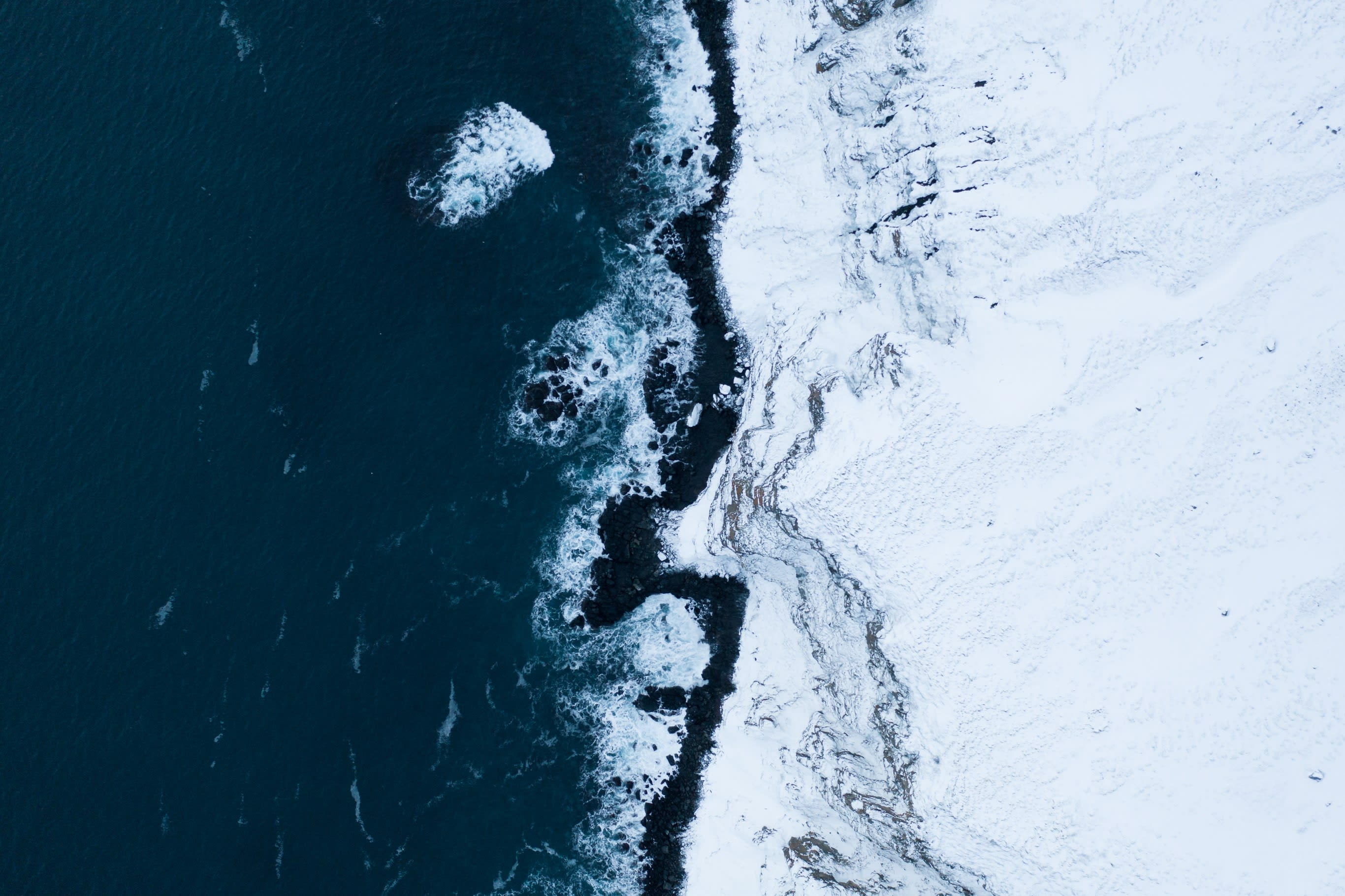 a birds eye view of the spot where a rugged mountain in Iceland meets the shore