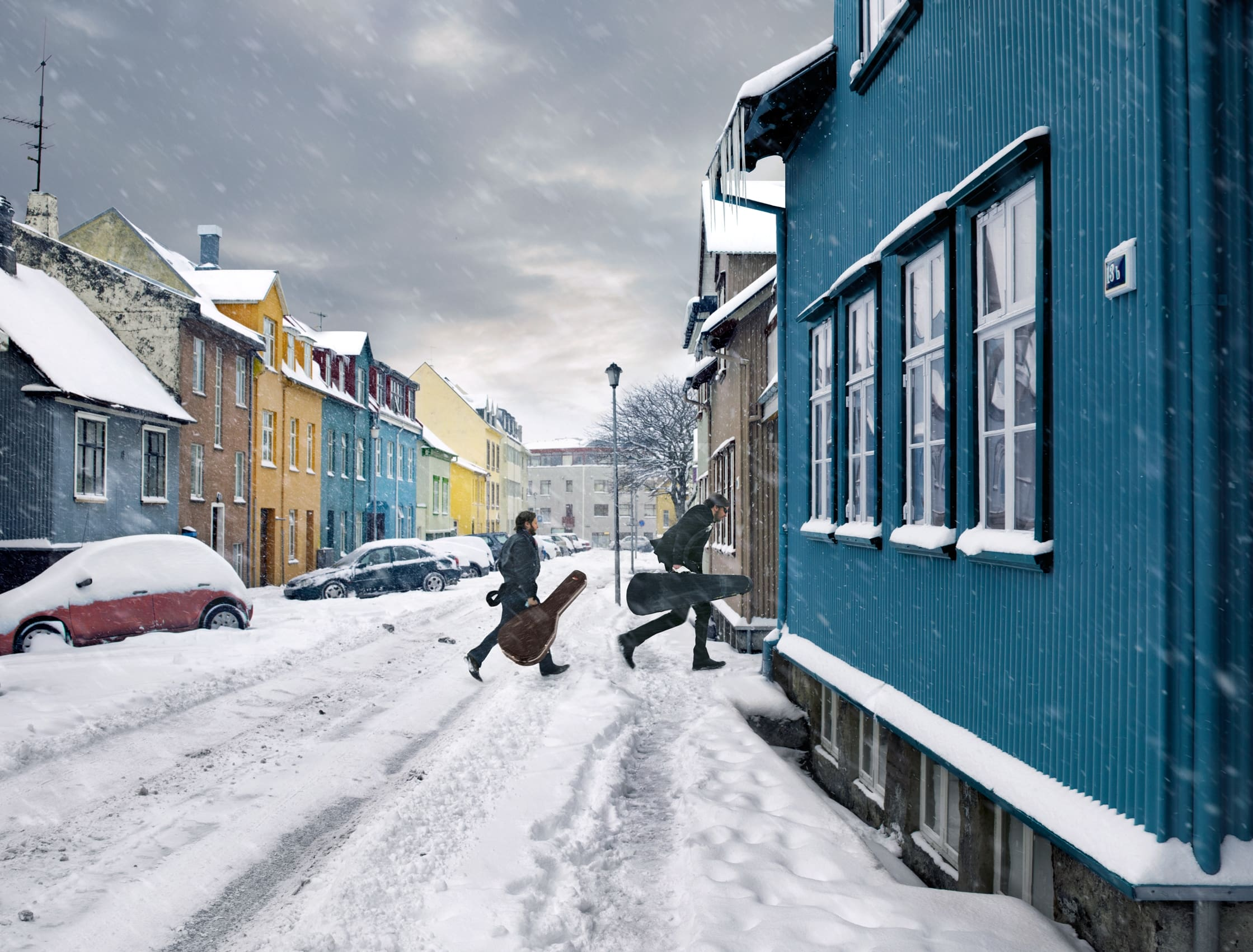 two musicians carrying musical instrument cases rush into a house in Reykjavik on a snowy day