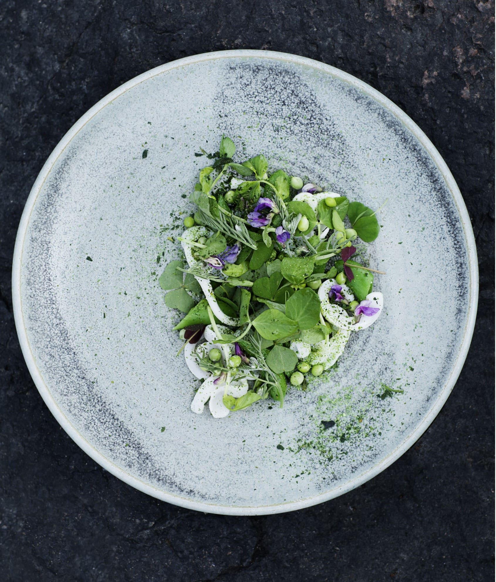 an overhead picture of a grey plate with a leafy vegetable salad dish upon it