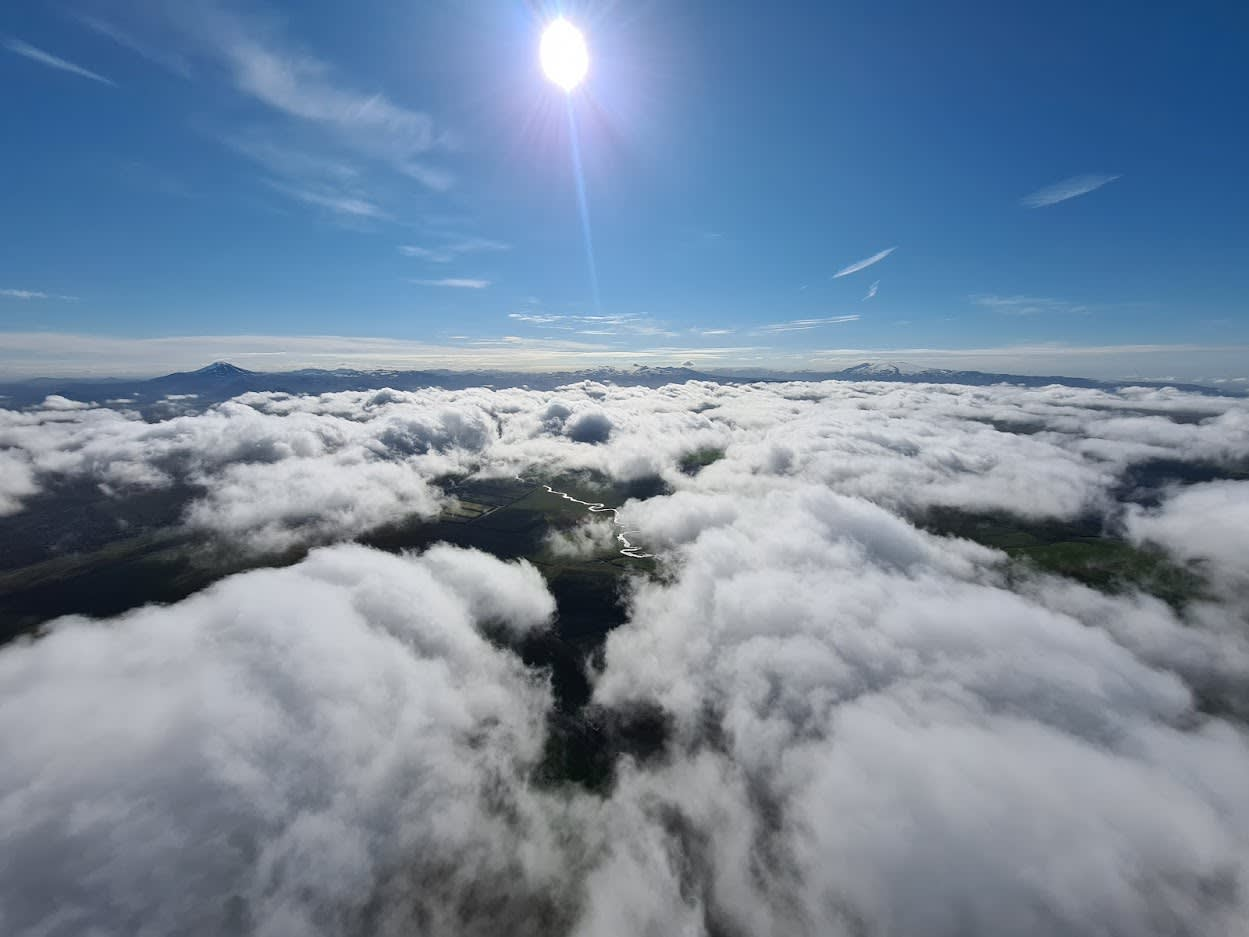 an aerial view of the landscape from the hot air balloon, with views from above the clouds and beneath to the land below