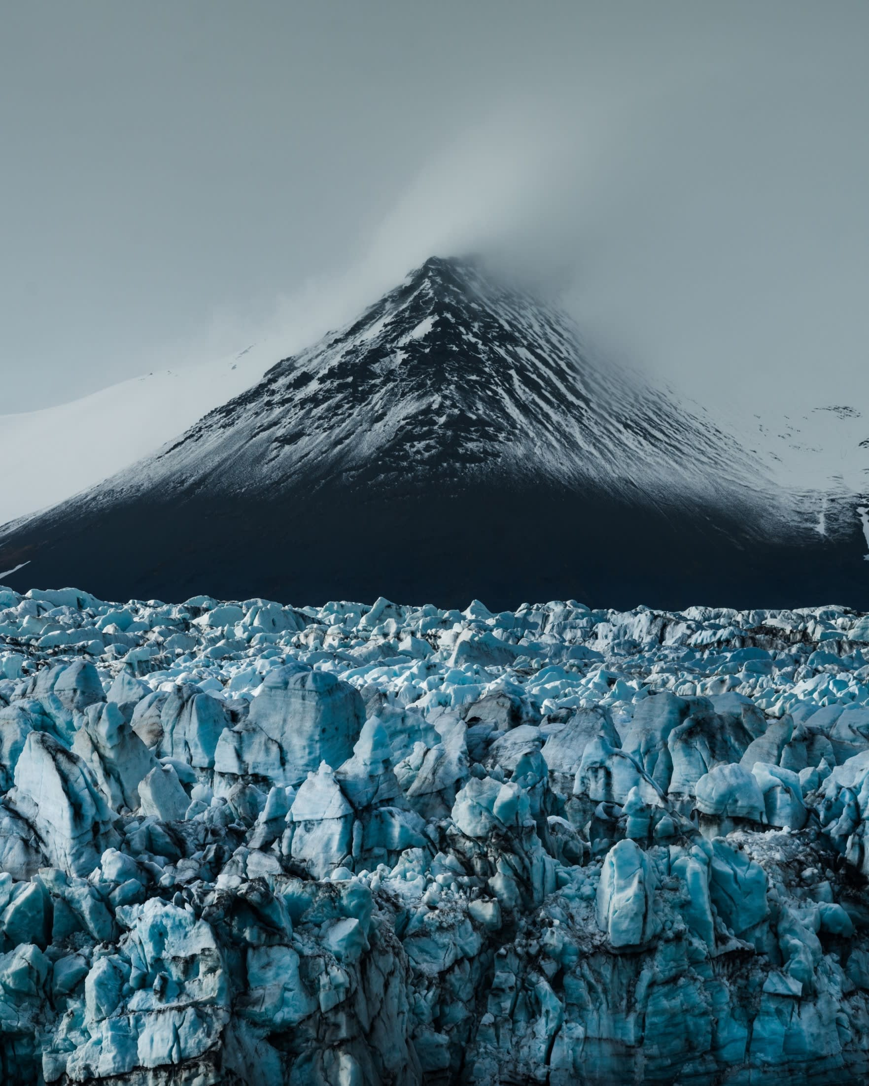 The bright blue Vatnajokull glacier in Iceland set against a snow covered mountain