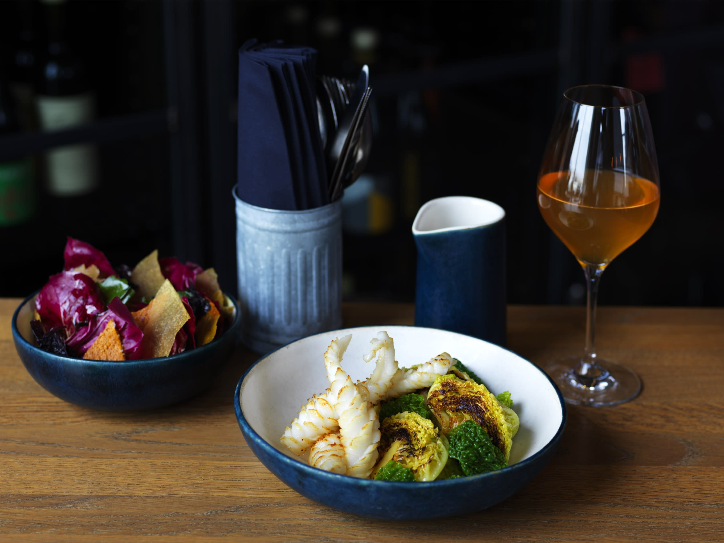 A fish and vegetable dish in blue and white bowls with a glass of bear and cultery positioned to the rear of the image