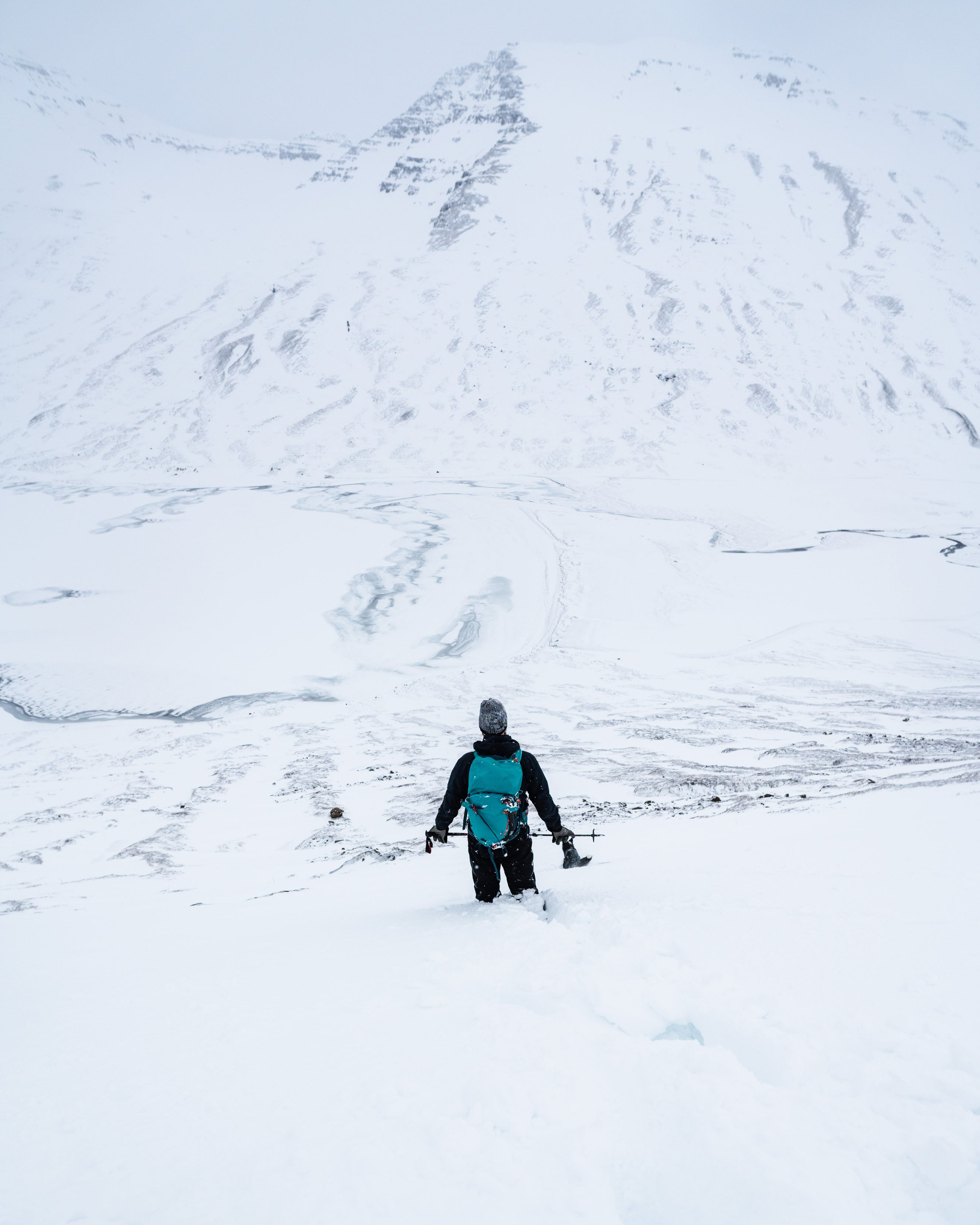 a person wearing all black with a blue backpack standing in a snowy Icelandic mountain region