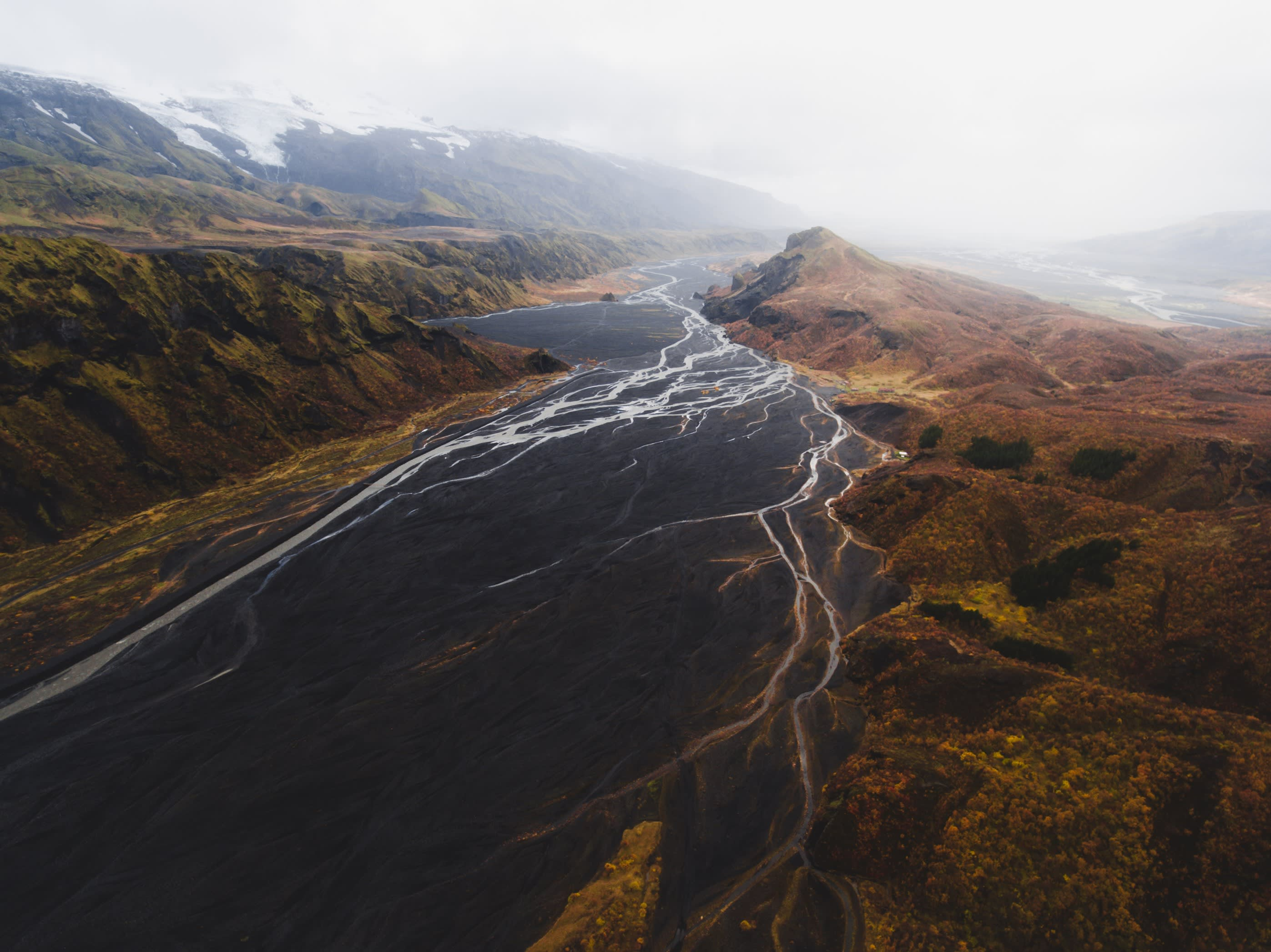 an aerial view of the mountains and glacier rivers at Langidalur and Valahnukur in Thorsmork, Iceland
