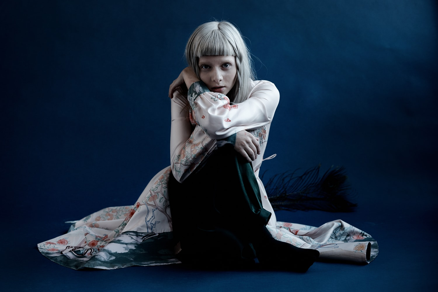 Artist Aurora pictured wearing a long white jacket with black trousers and sitting in a huddled position