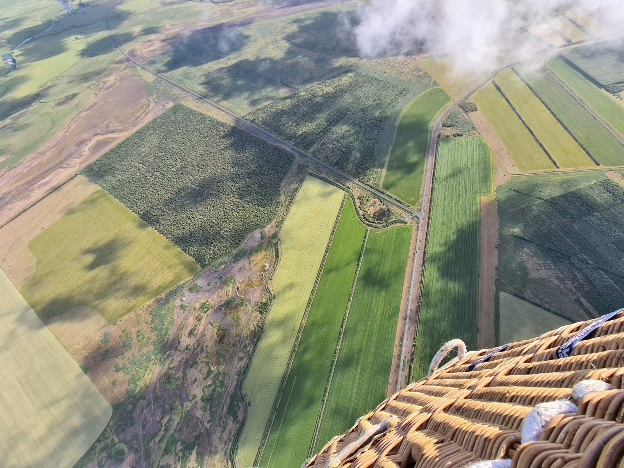 a view from within the basket, with a partial view of the basket and views looking down to the farmers fields below