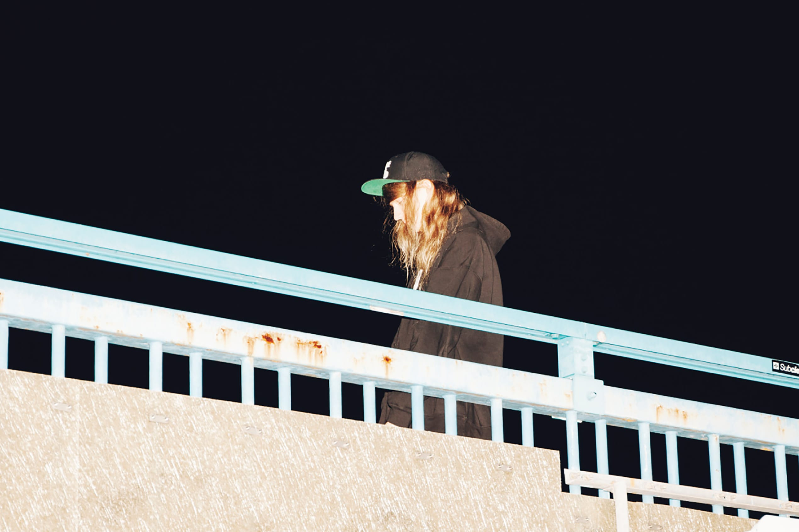 Musician Cashmere Cat is pictured at night walking across a bridge in Reykjavik, wearing a black hat and hoodie