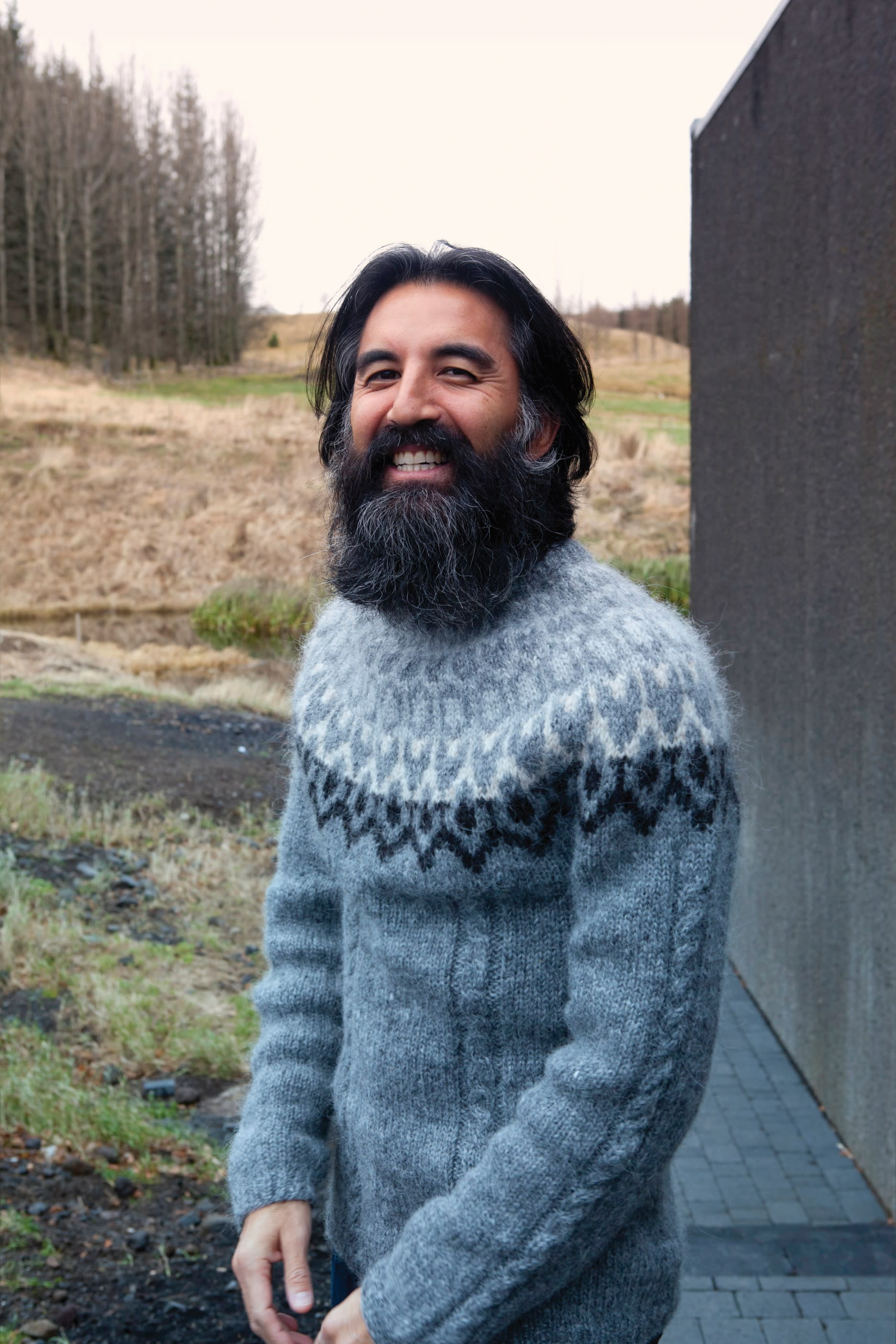 a man with a large beard, standing in the Icelandic nature, smiling directly into the camera while wearing a grey knitted Icelandic sweater