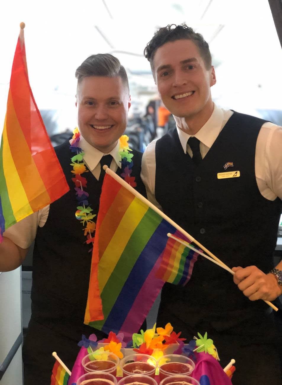 Two members of Icelandair cabin crew pictured flying the flag for Pride within the aircraft