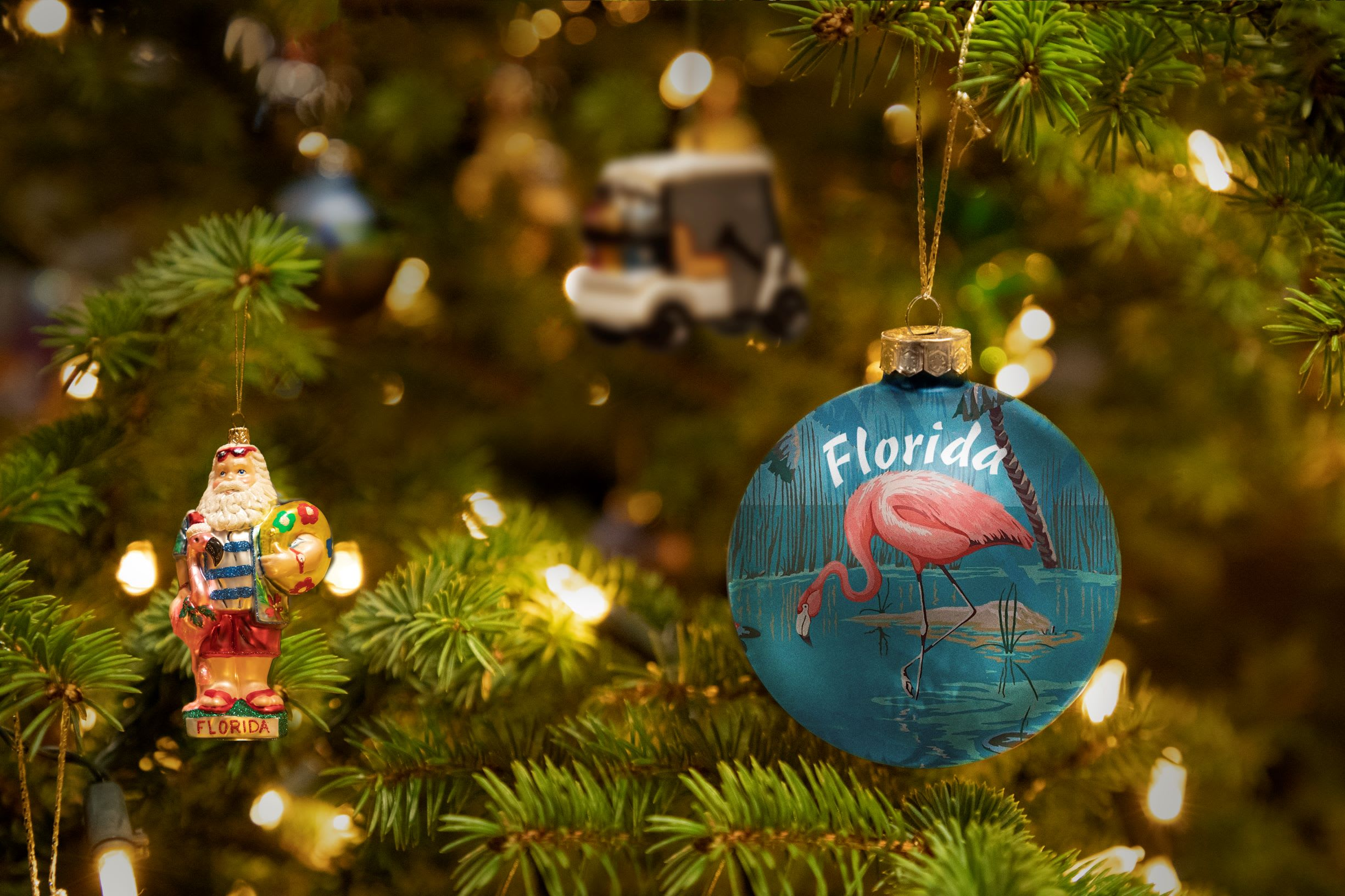 a Christmas tree up close with a large blue bauble in the foreground that reads 'Florida' and has a pink pelican on it