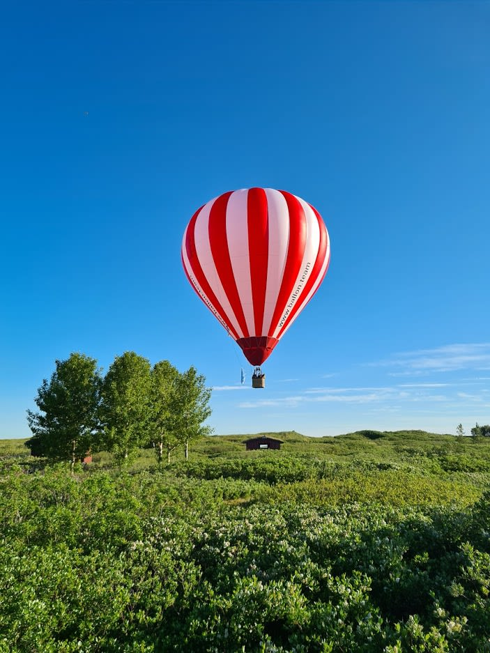 a red and white striped hot air balloon floating above a lush green landscape in Iceland