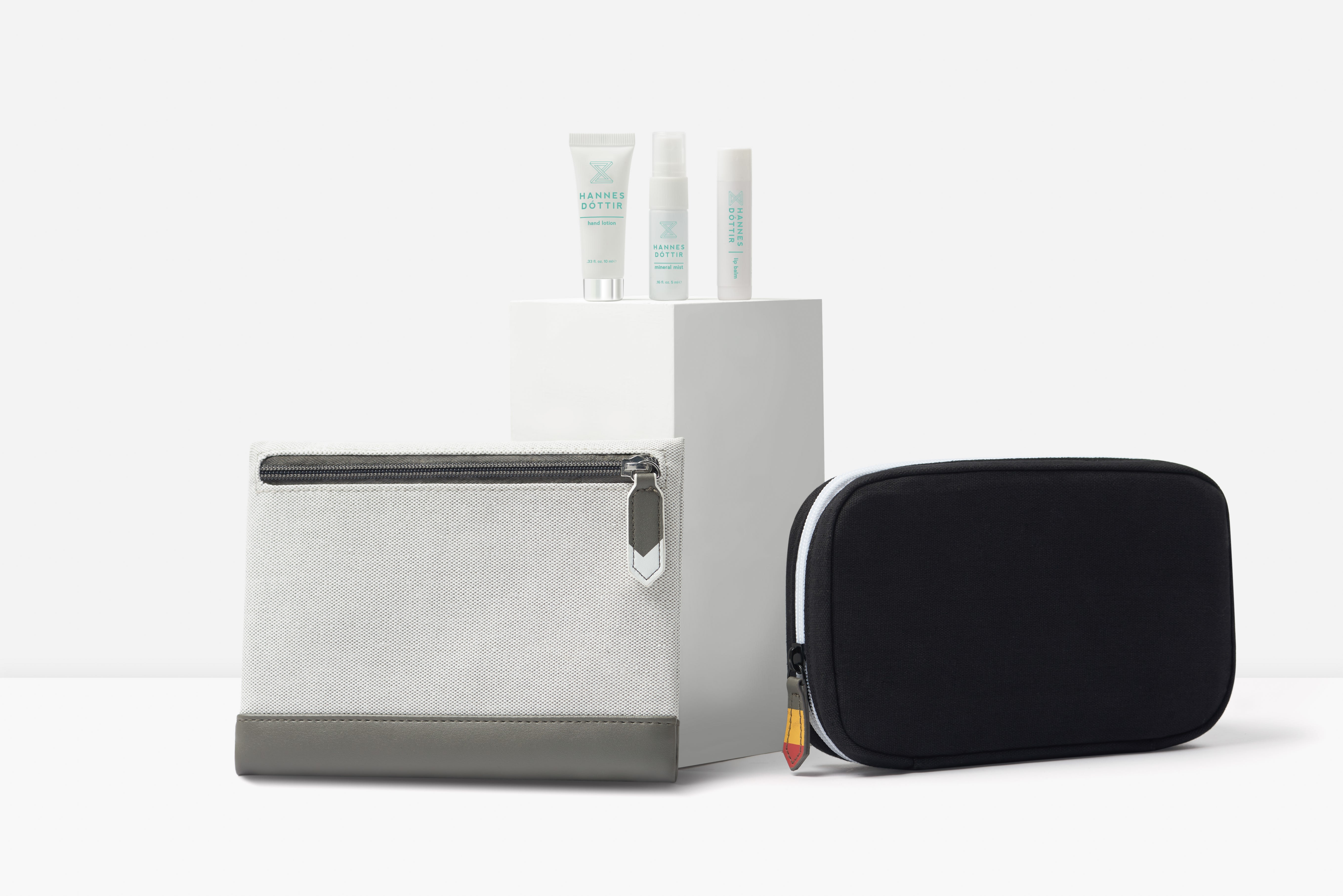 Icelandair's two new amenity designs shown side by side with some toiletries placed on a pedestal behind the bags