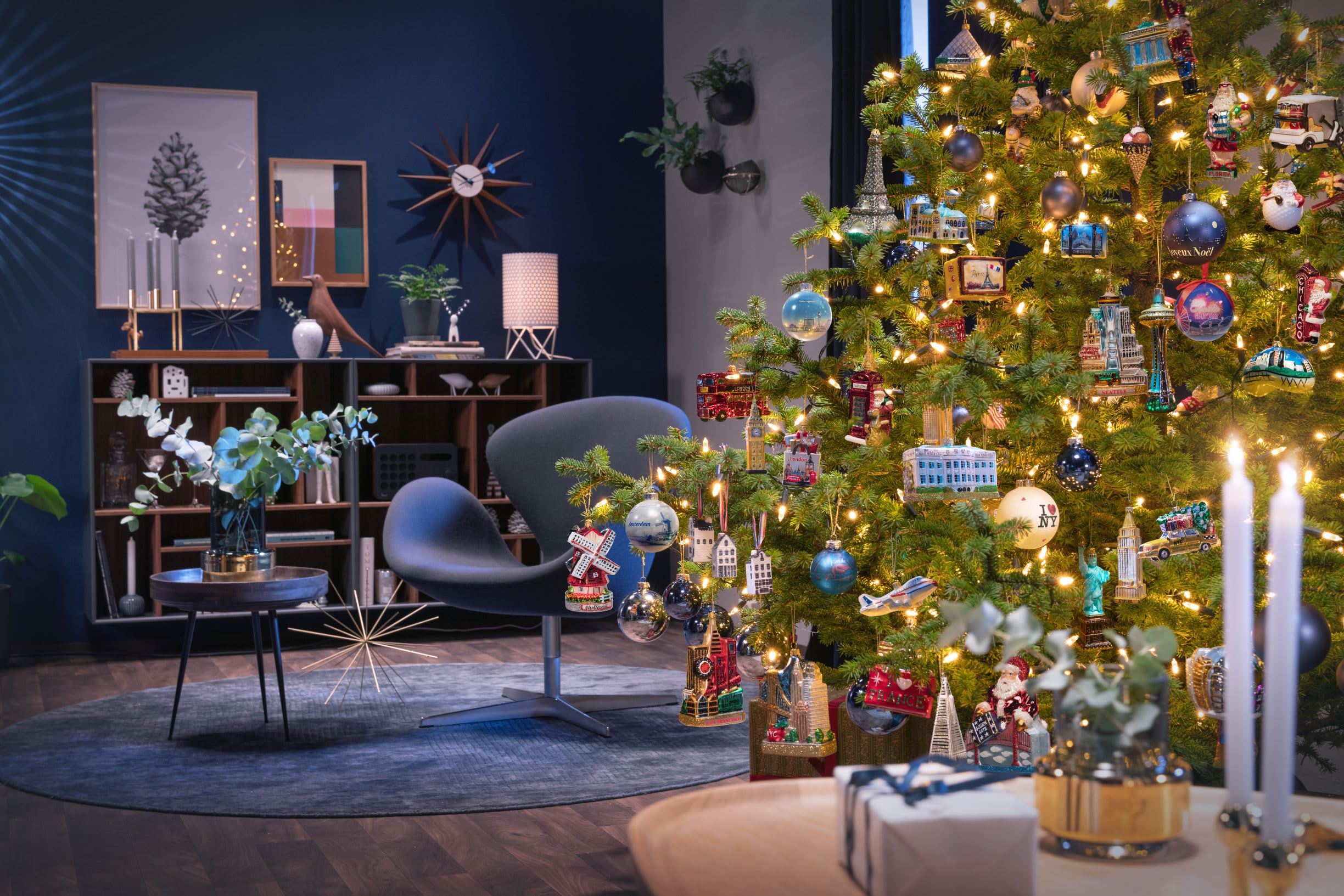 a cosy livingroom scene with designer Scandanavian decor and a large bright Christmas tree