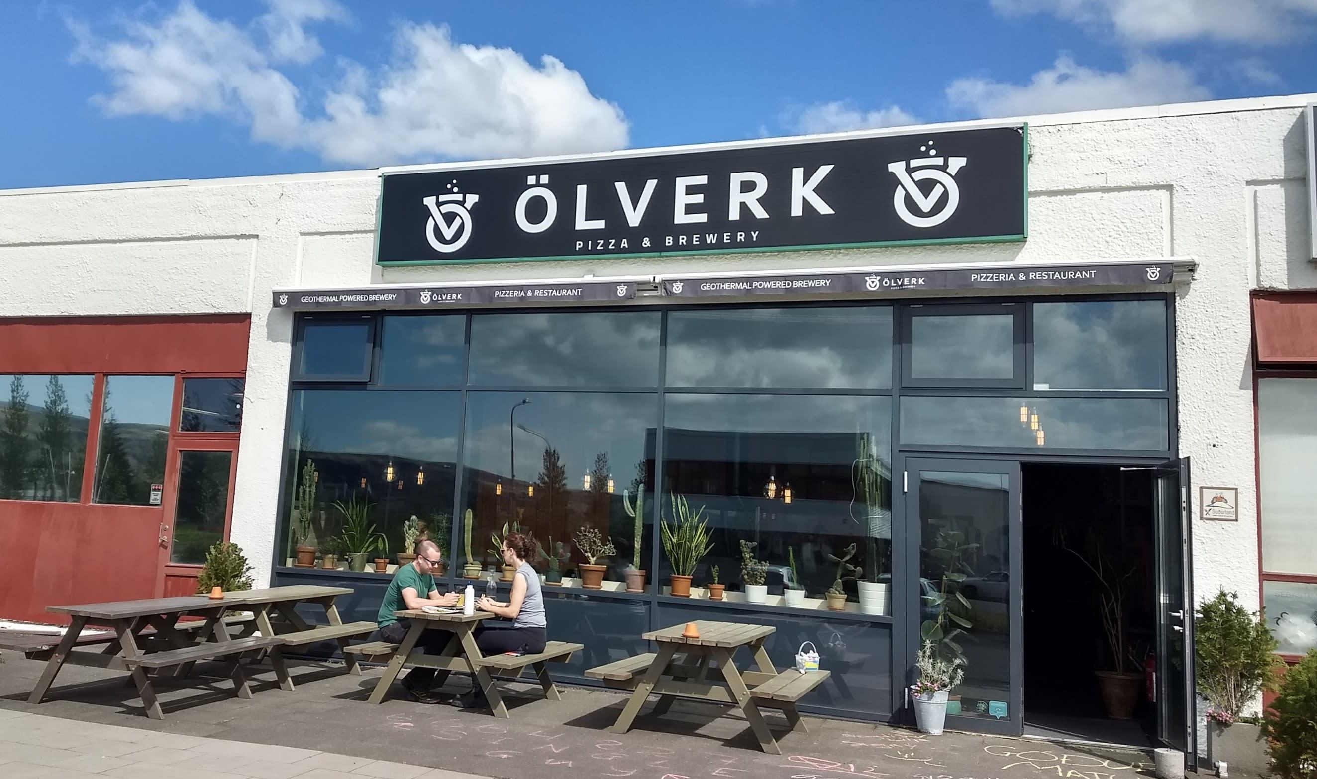 two people enjoy beer and pizza outside Olverk brewery in Hveragerdi in Iceland