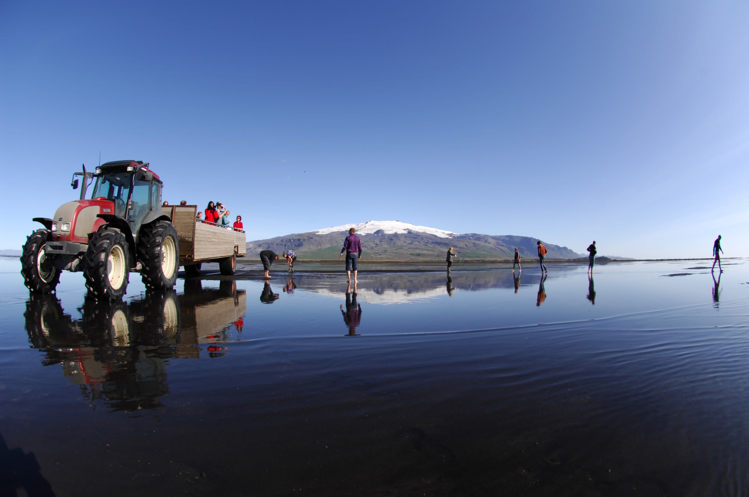 A tractor parked on a wet black sand beach on route to Ingolfshofdi