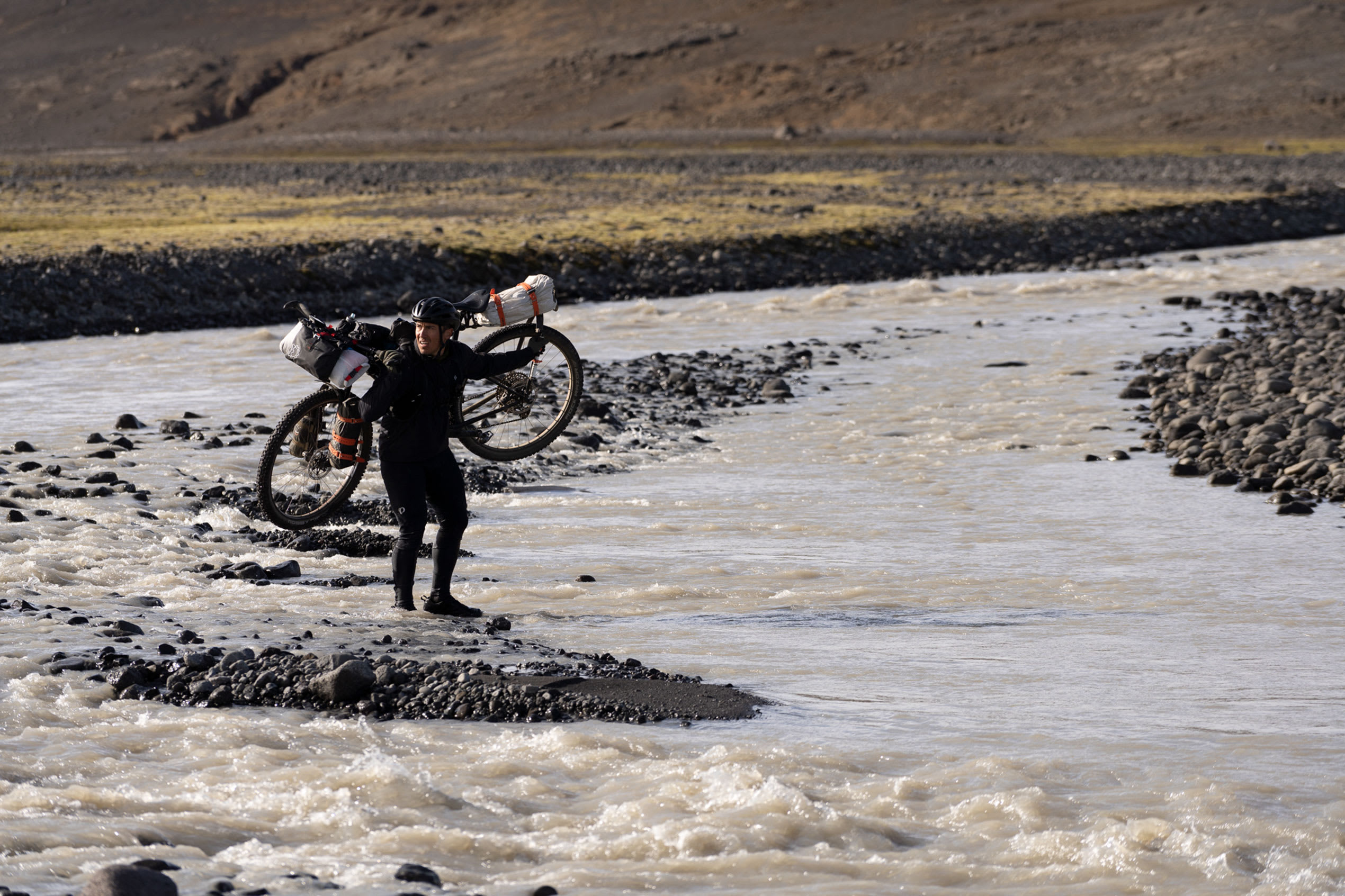 an image of a man carrying a bike over his shoulders and walking through a river in Iceland