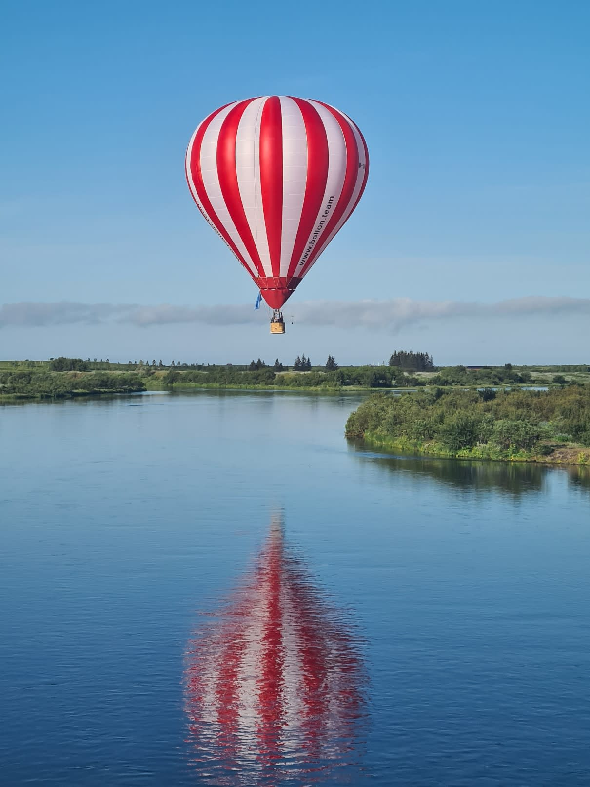 a red and white striped hot air balloon flying over a body of water in South Iceland