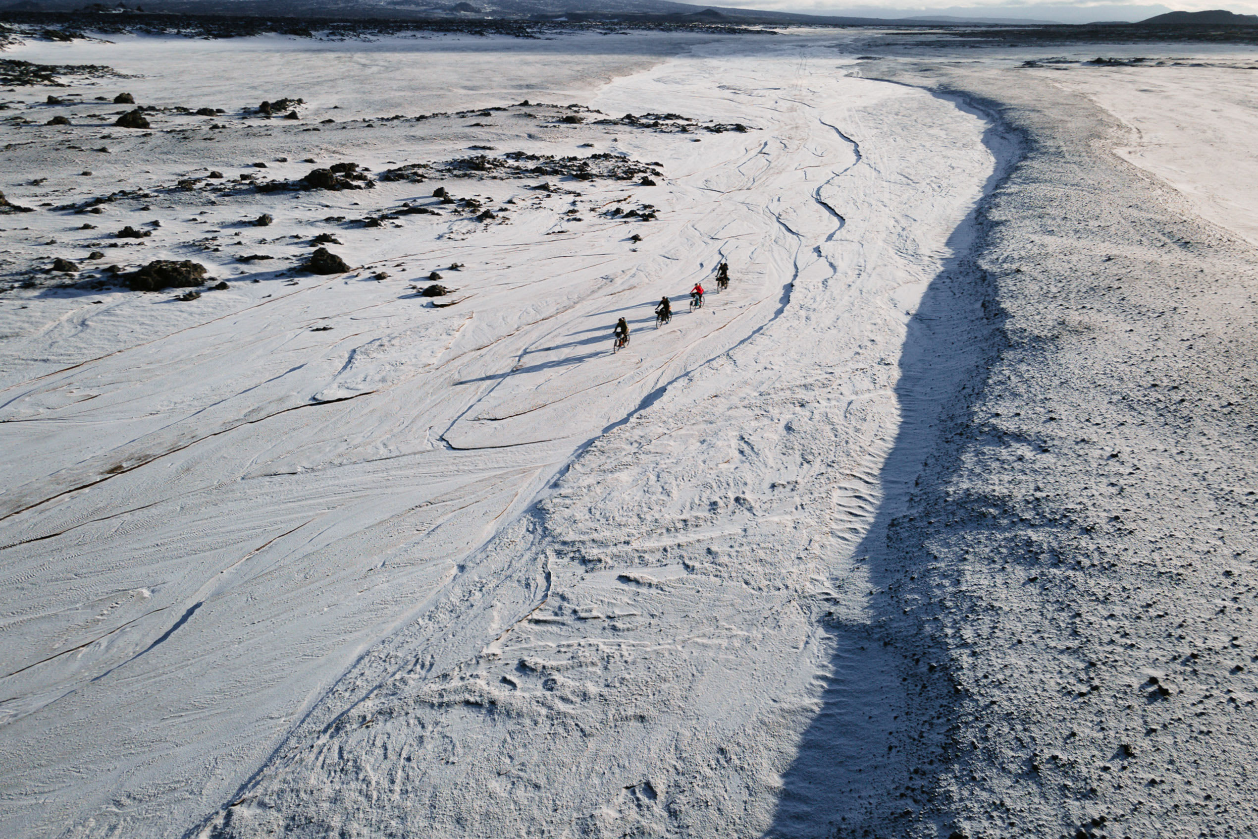 an overhead view of four bikepackers making their way through the snowy Icelandic landscape