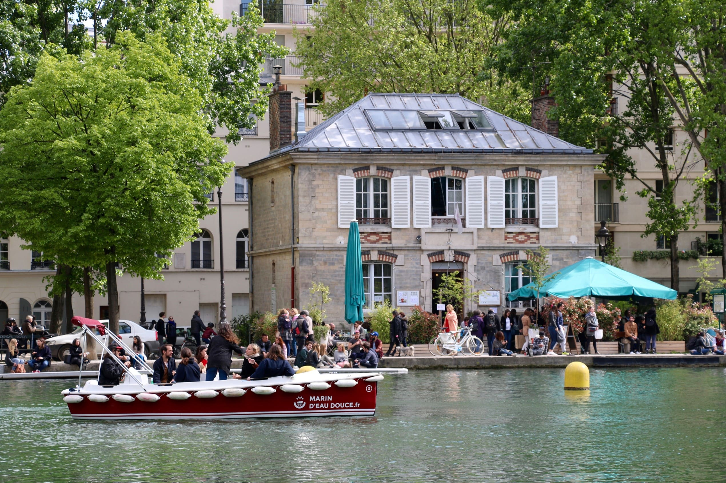 The canal de l'ourcq in Paris with a bustling cafe and riverway