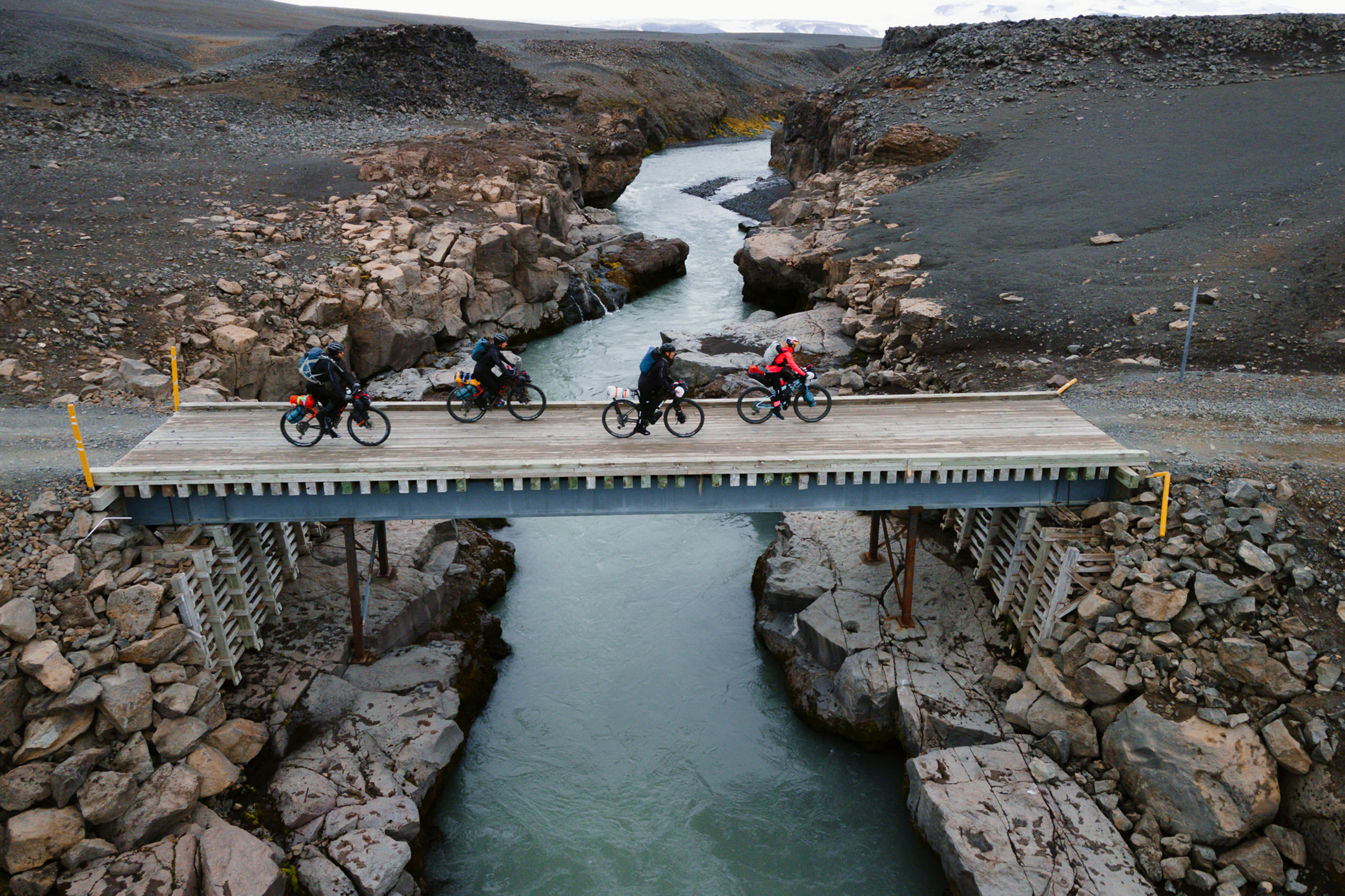 a group of four cyclists bikepacking their way through Iceland, crossing a bride over a river