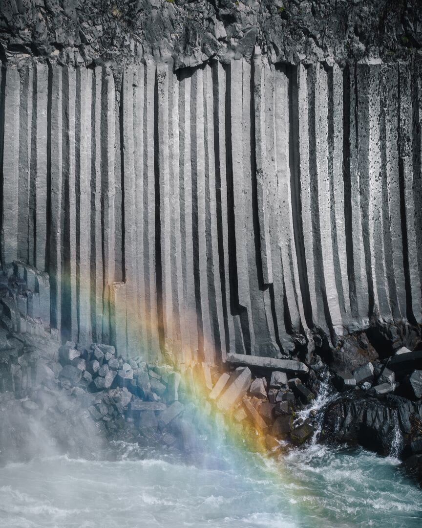 A rainbow reflected in the water spray as the waves crash against the basalt columns that are symbolic of the Icelandic landscape