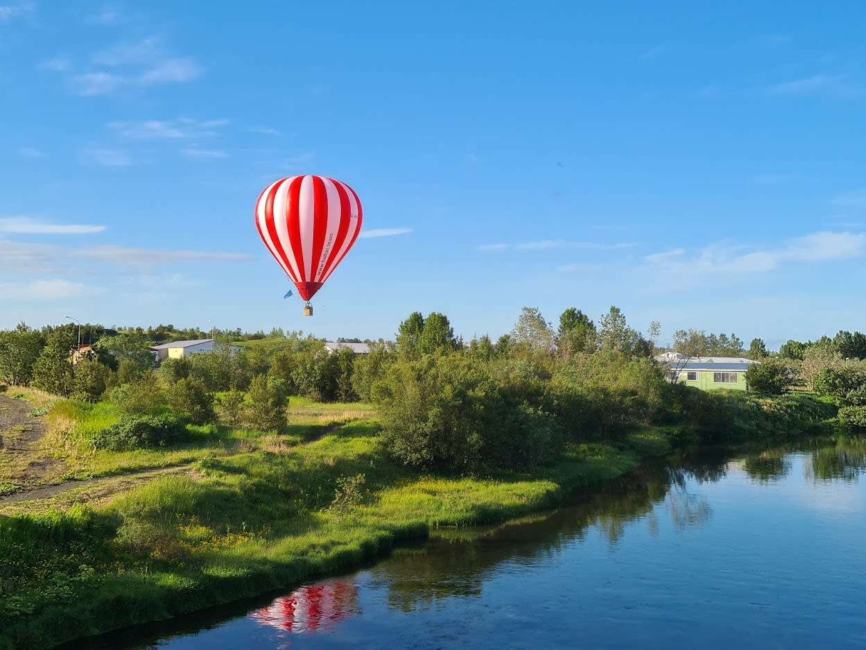 a red and white striped hot air balloon flying over the leafy green Icelandic landscape next to a body of water