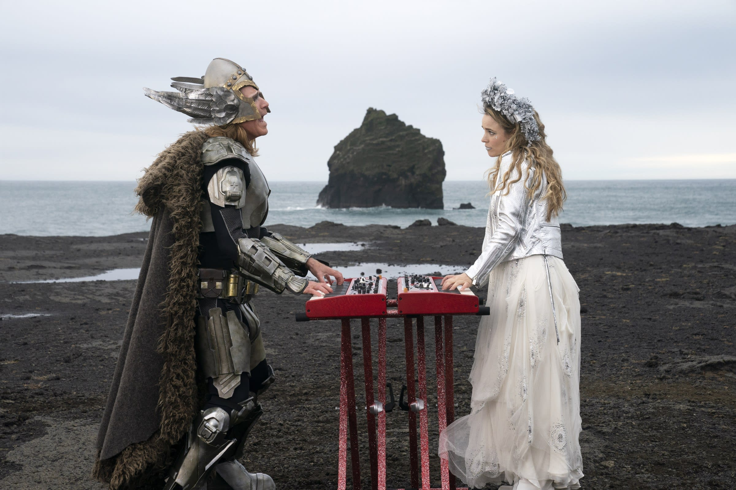 Will Ferrell and Rachel McAdams pictured playing two keyboards while looking at one another and singing. The scene is set amidst the Icelandic landscape