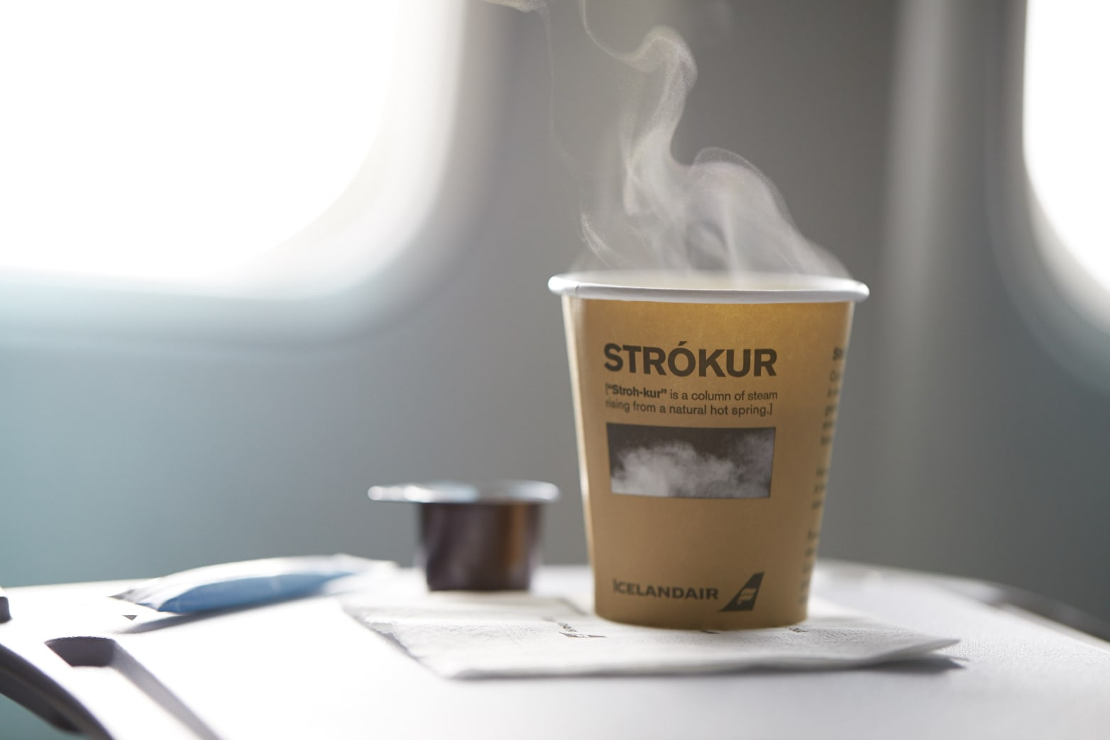 a brown paper cup with a steaming hot drink within it and text printed upon it that reads 'Strokur'