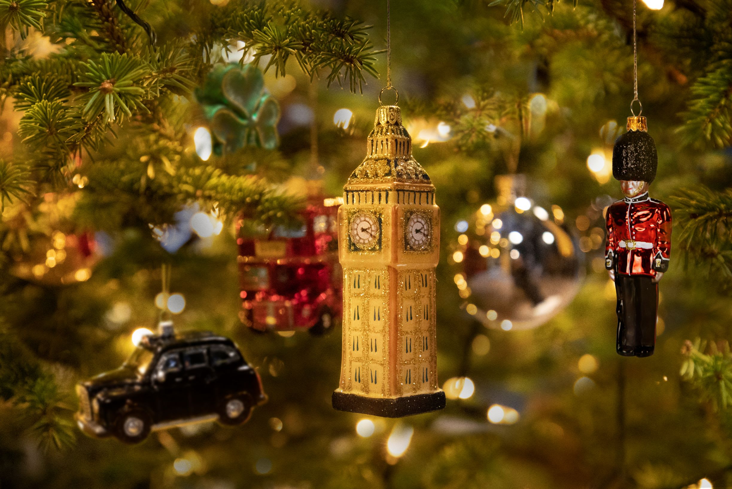 an up close Christmas tree with British themed decorations including Bi9g Ben, a black cab and a Queen's guard