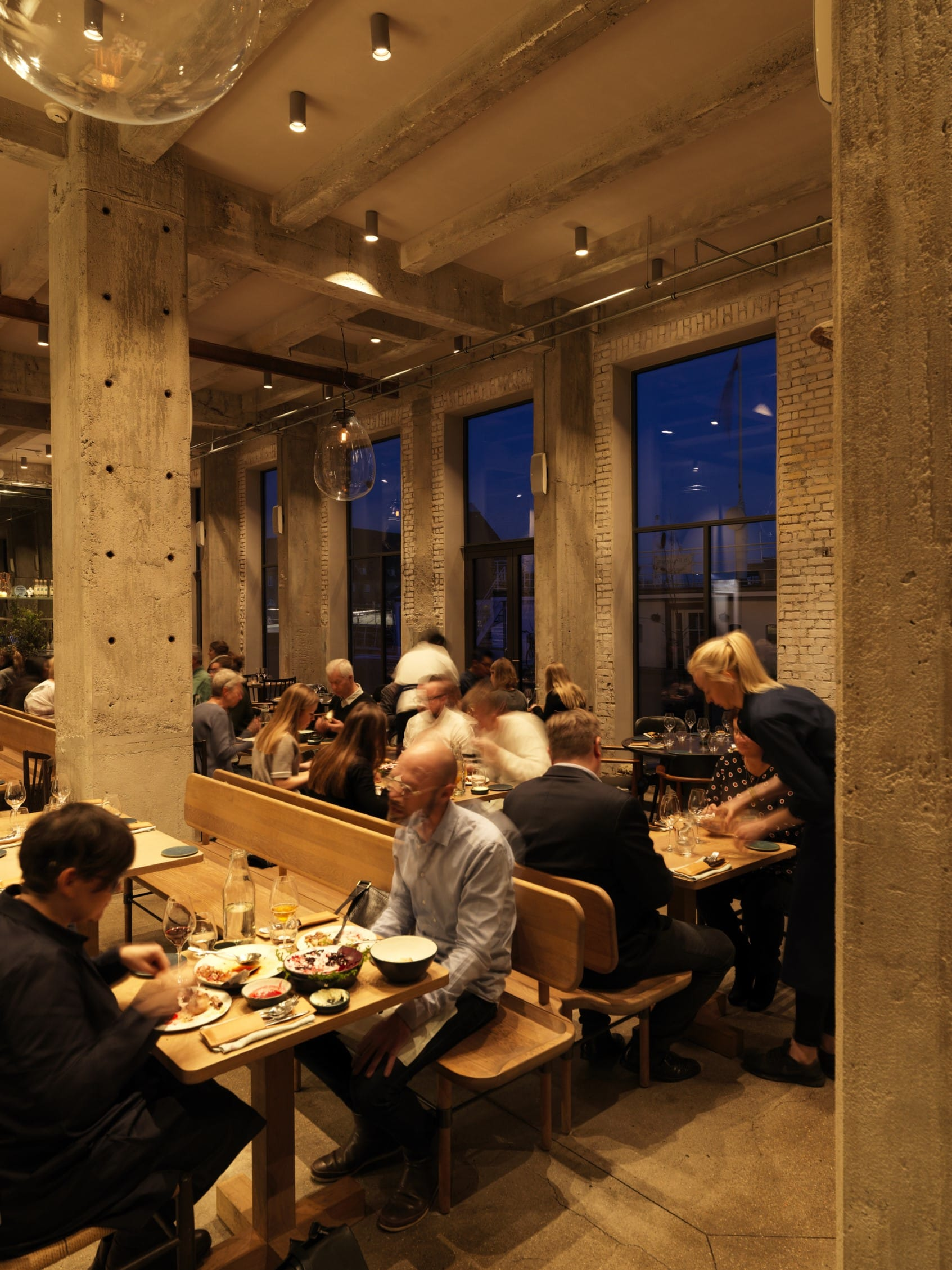 a bustling restaurant called 108, where diners eat at rows of wooden tables with benches