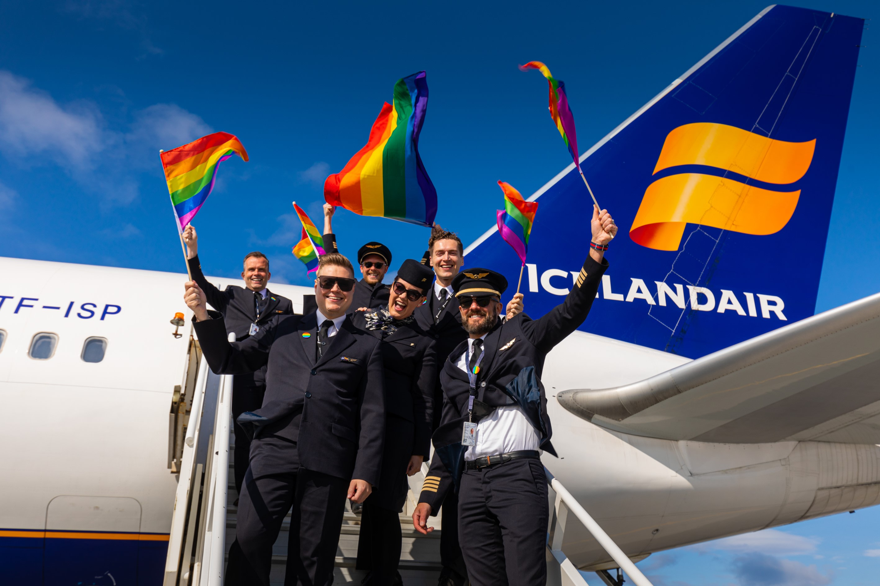 A group of Icelandair staff standing on the aircraft stairs flying the flag for Pride
