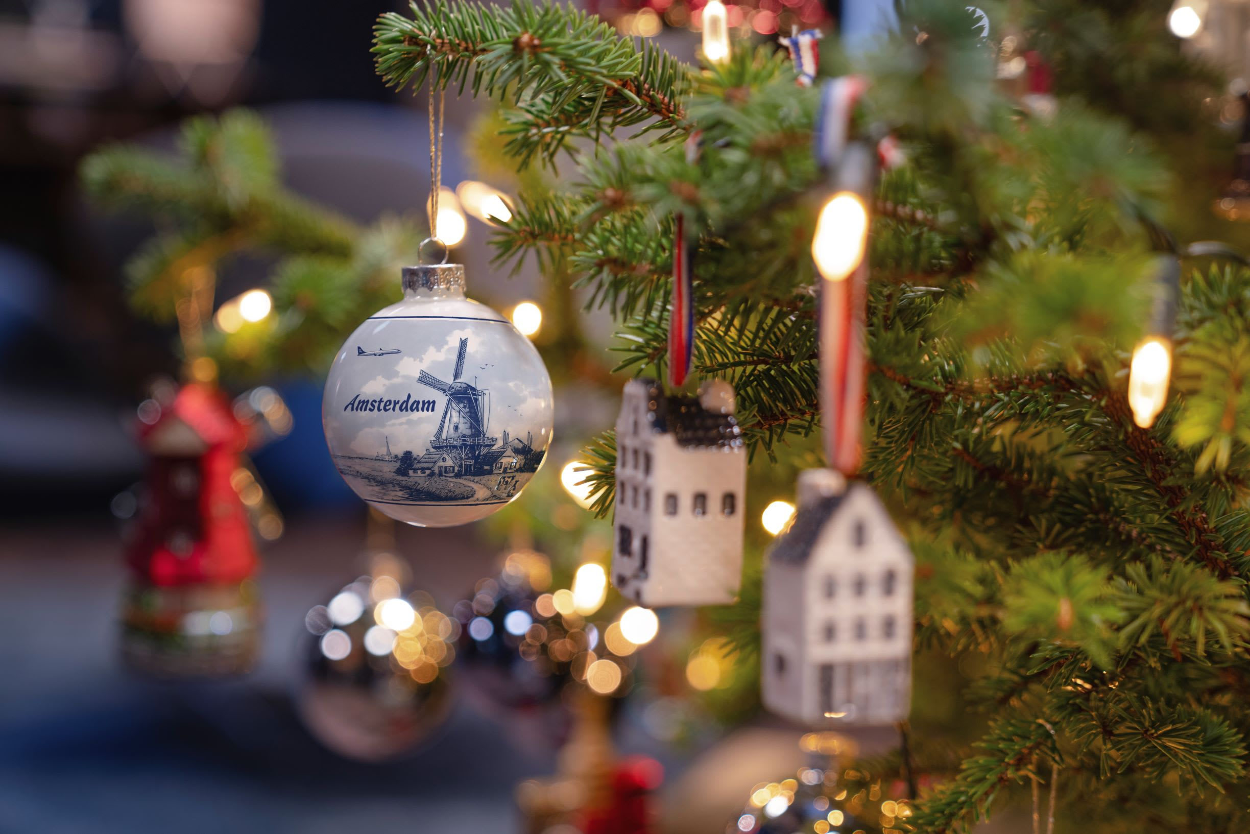 an up close of a Christmas tree with a bauble with a windmill on it and copy that reads 'Amsterdam'