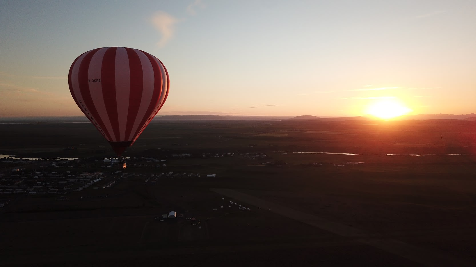 a red and white hot air balloon pictured flying over the South Iceland landscape at golden hour
