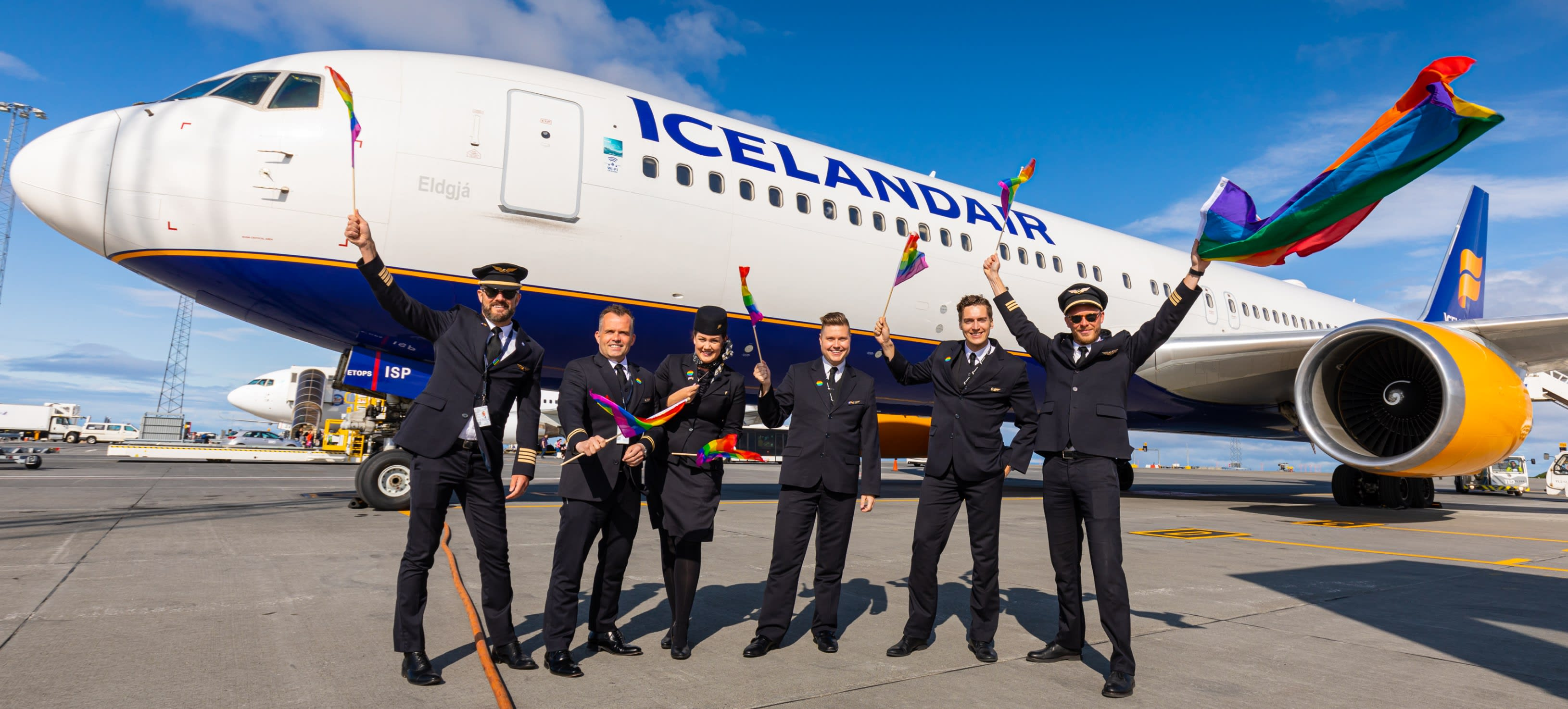 A group of airline staff flying rainbow Pride flags as they stand outside an Icelandair aircraft