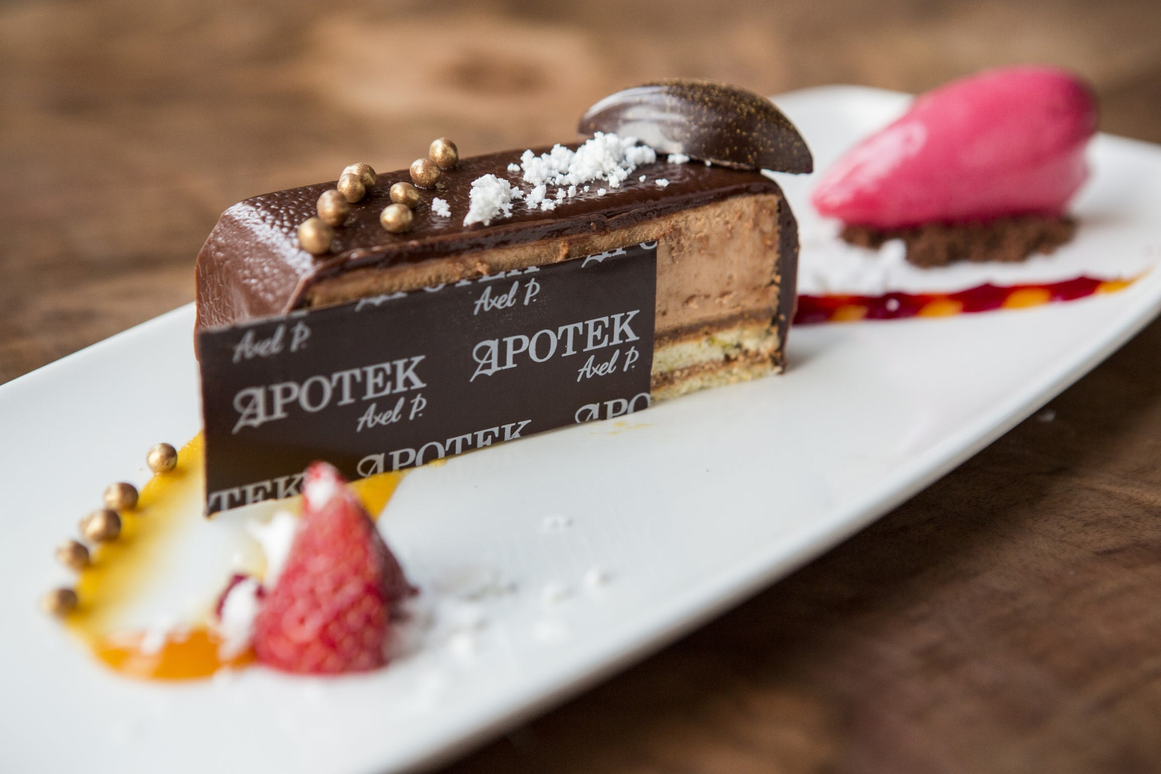 a close up of a chocolate cream cake with a chocolate decoration that reads 'Apotek'