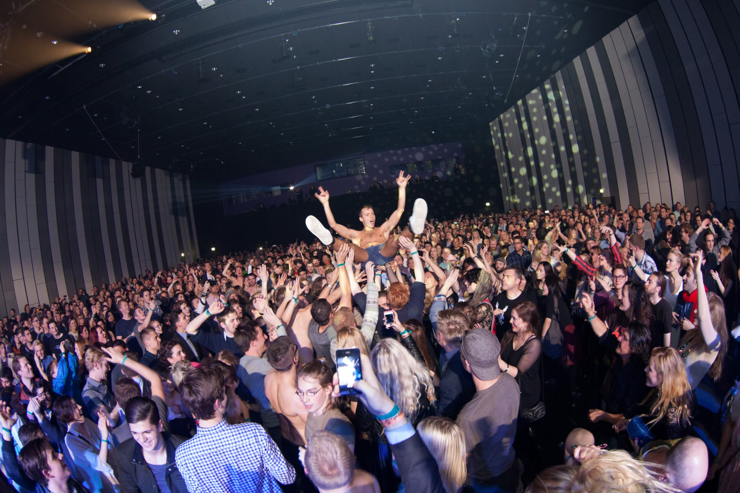 a lively crowd lifts somebody up above head and allows them to crowdsurf