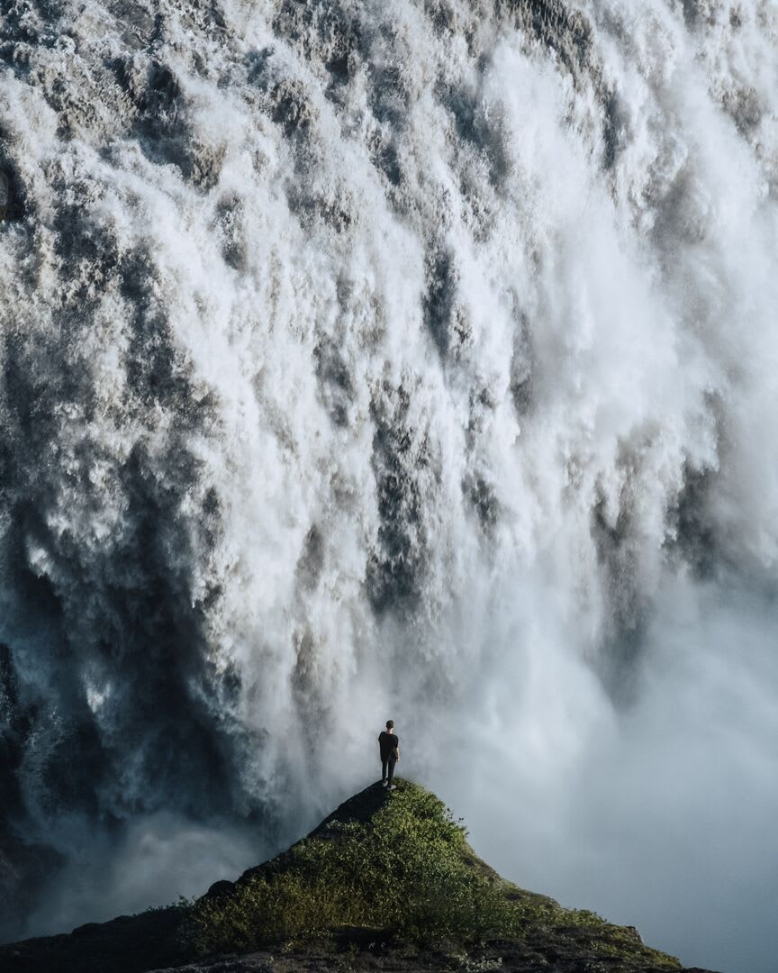 A close up image of Dettifoss waterfall with a person silhouetted in the foreground