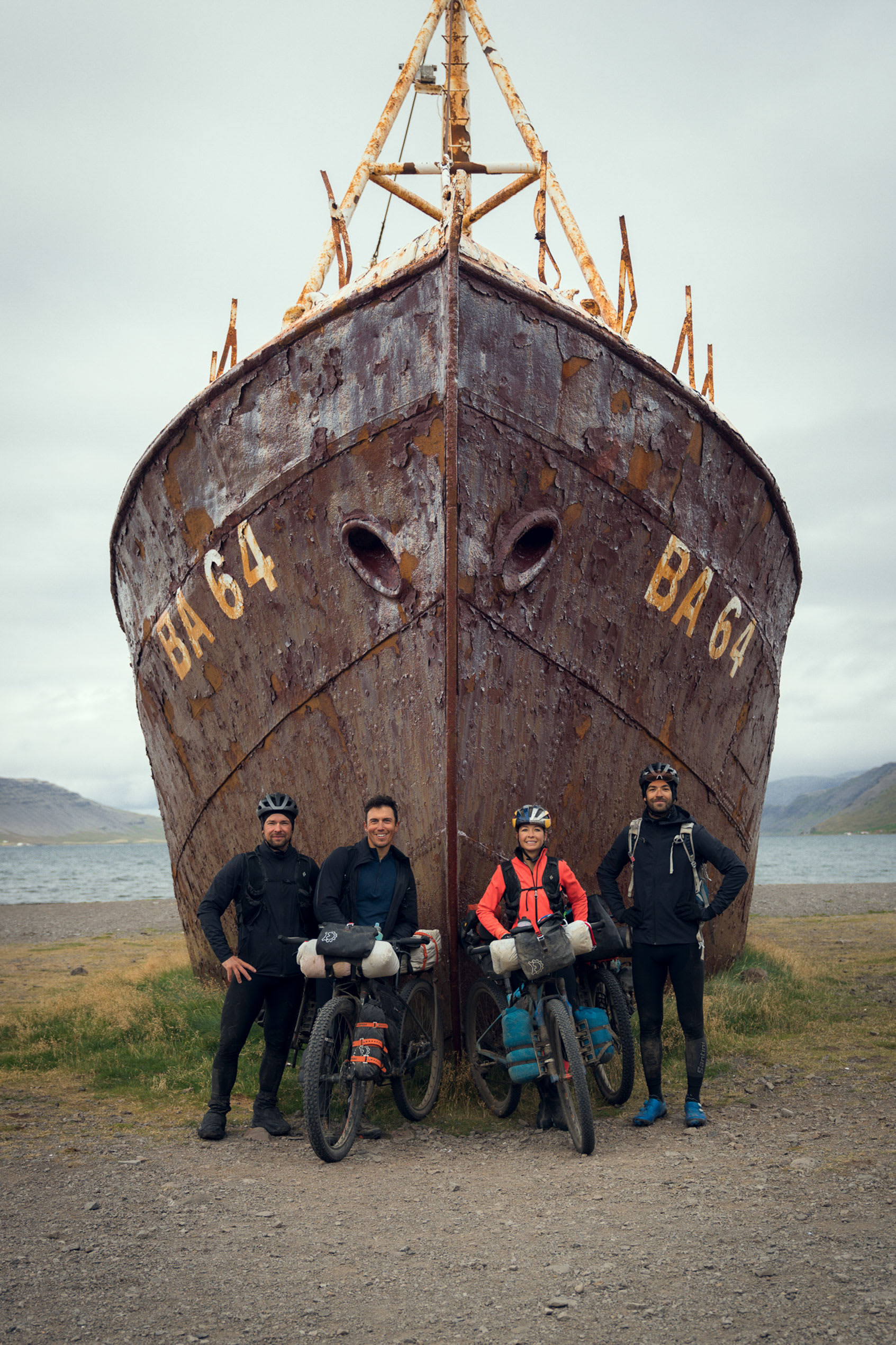 four cyclists pictured smiling directly into the camera, standing in front of a large boat which has been beached