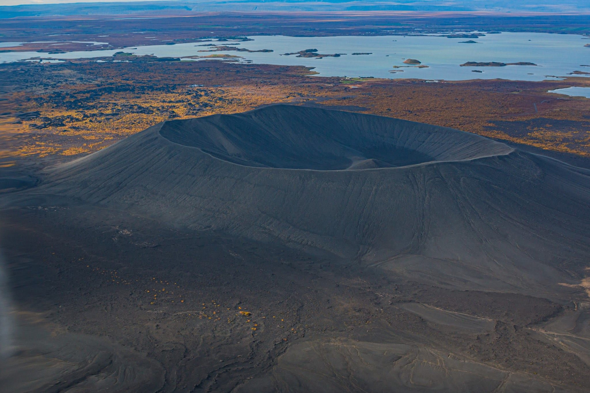 One of Myvatn's large craters pictured from above with views behind of the blue waters and volcanic landscape