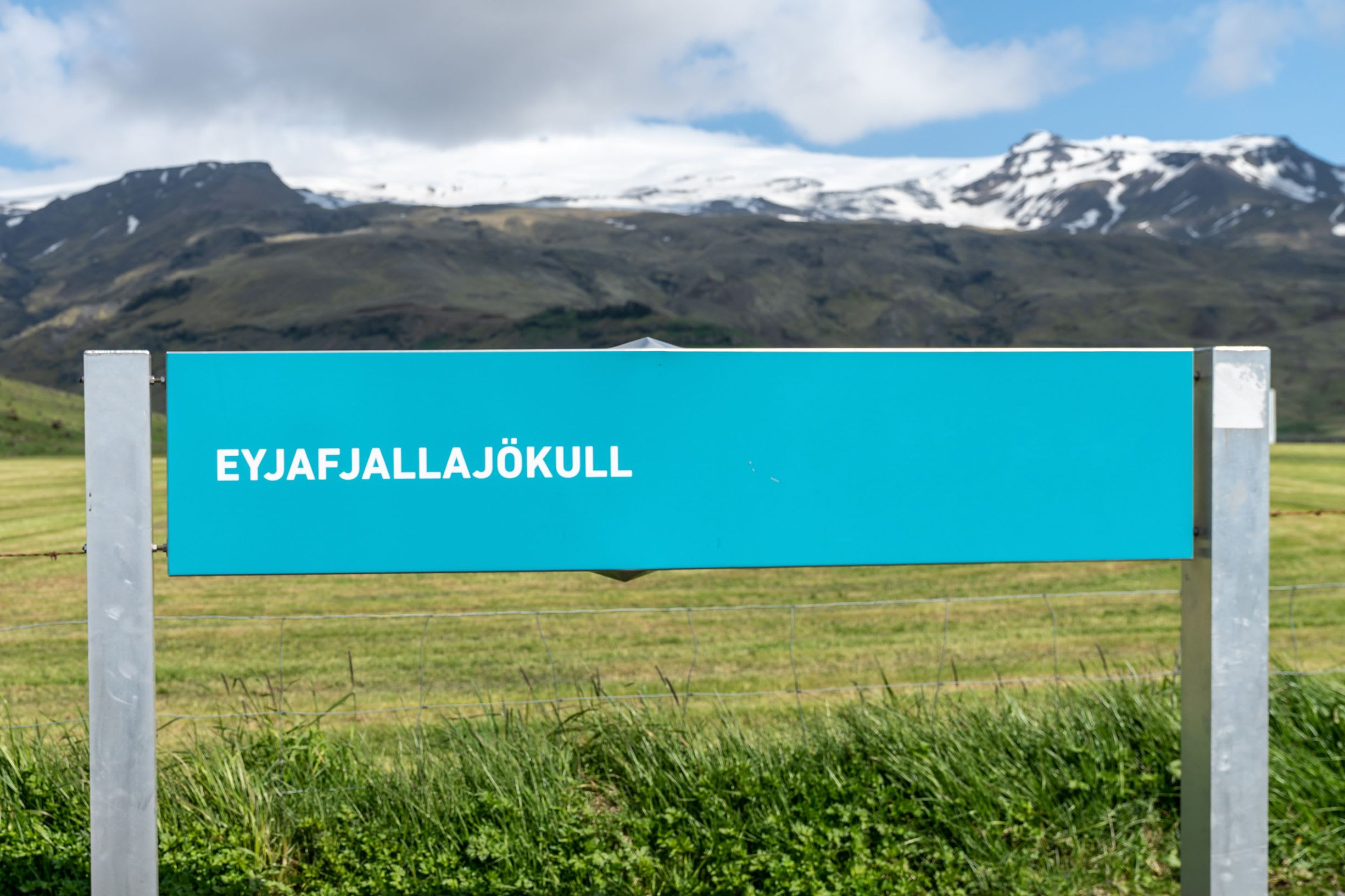 a blue sign that reads 'Eyjafjallajokull', the name of the famous volcano which was responsible for the 2010 eruption. The sign is positioned within the Icelandic nature