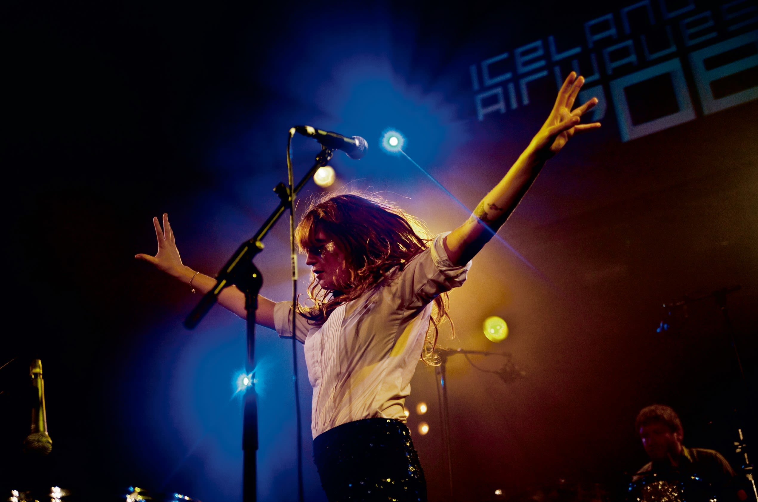 Florence and the Machine performing on-stage with her arms spread wide in dance