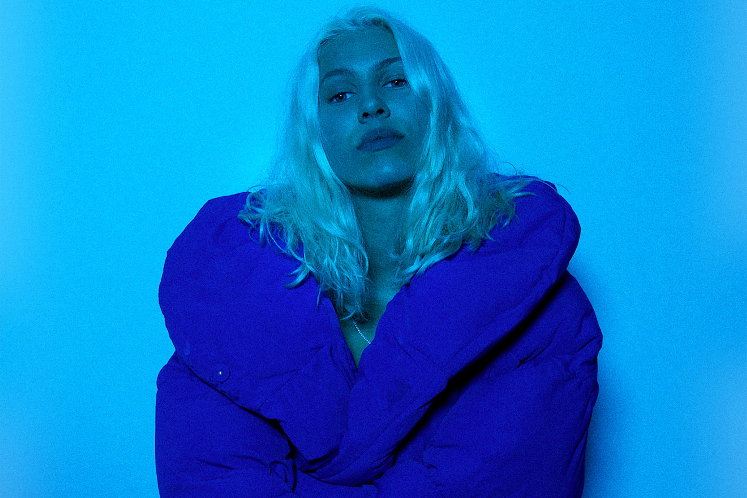 Musician Bríet pictured wearing a bright blue jacket in a blue lit room