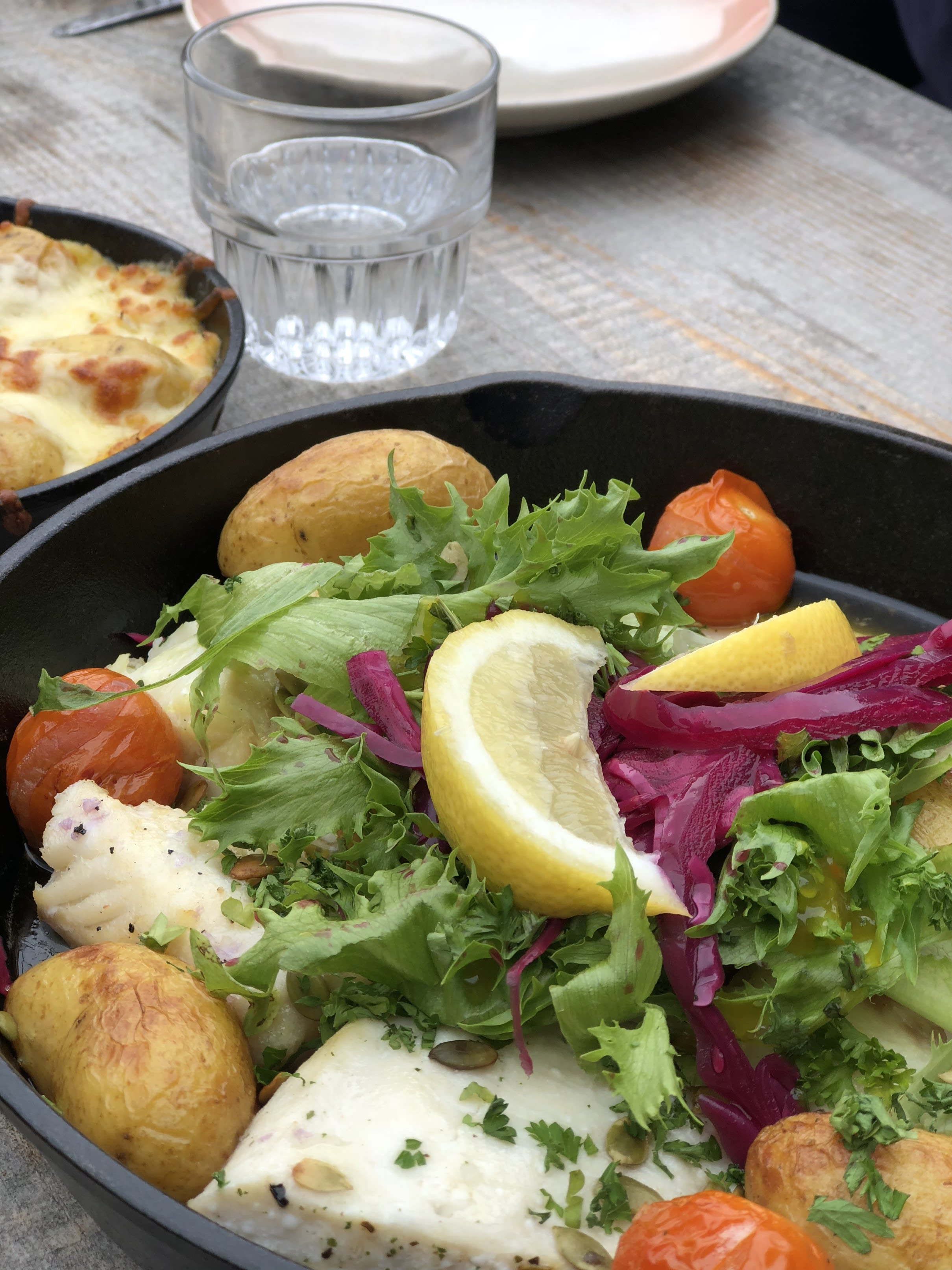 a close up of a dish with fish, salad, potatoes, cabbage and lemon in a black oven dish