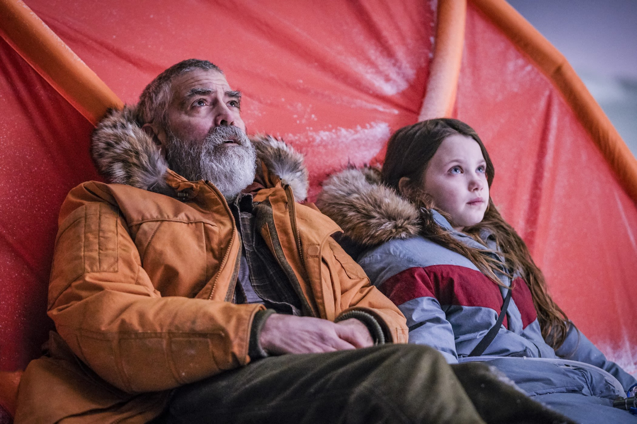 George Clooney pictured next to seven year old actress, Iris, leaning against a red tent-like structure