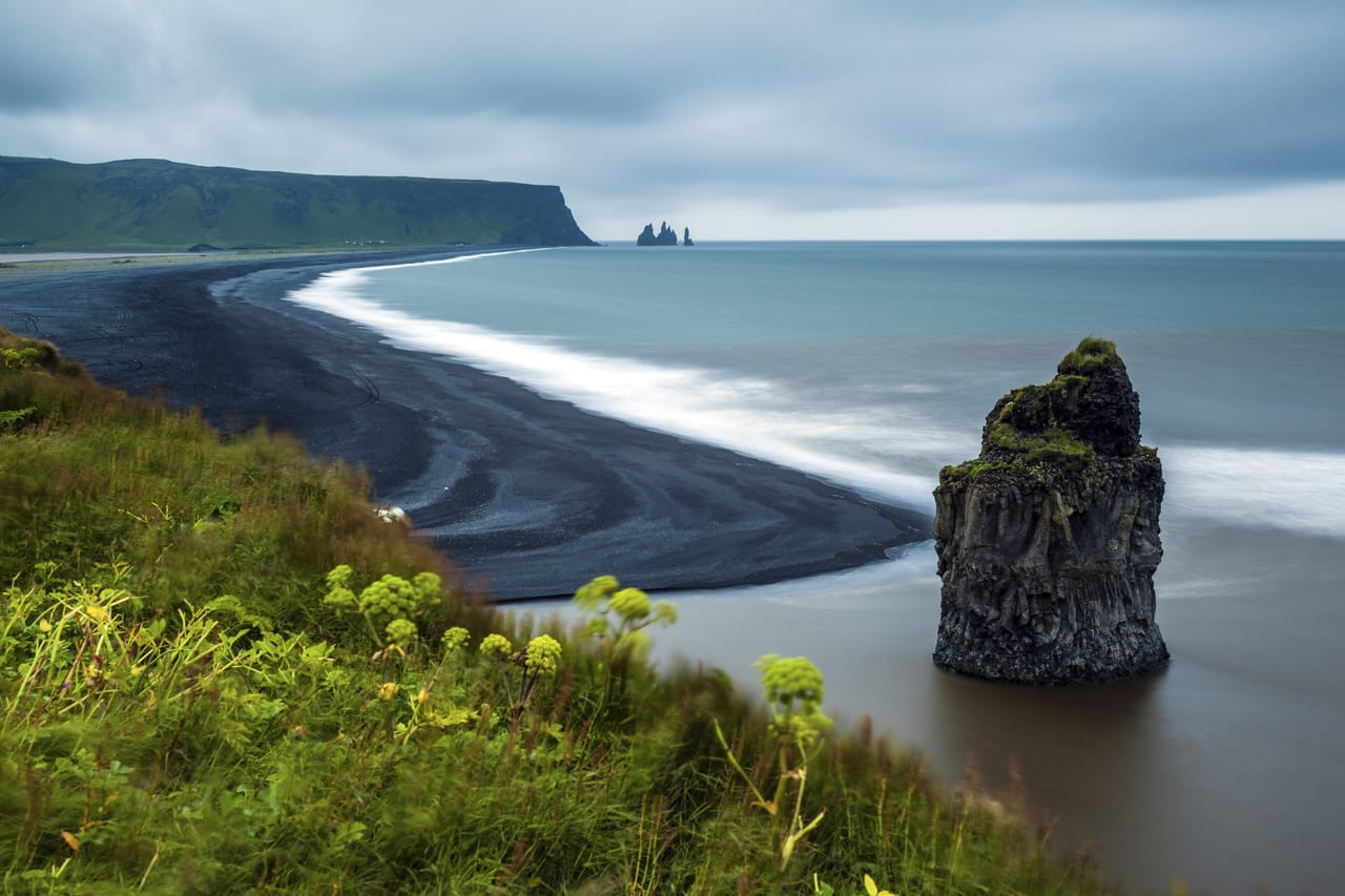 Reynisfjara black sand beach viewed from a hilltop, with the view looking out on to the sea stacks and basalt black columns