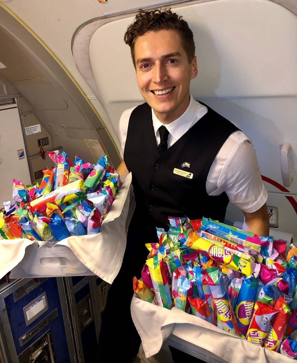 A member of Icelandair cabin crew smiling directly into the camera and holding two baskets - one in each hand - full of Icelandic candy called Staur