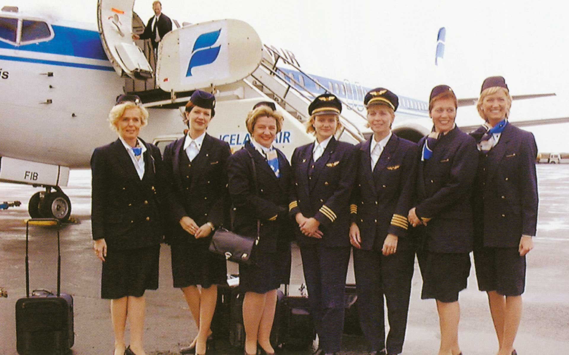 a group of female Icelandair staff wearing full uniform standing in front of an Icelandair airplane