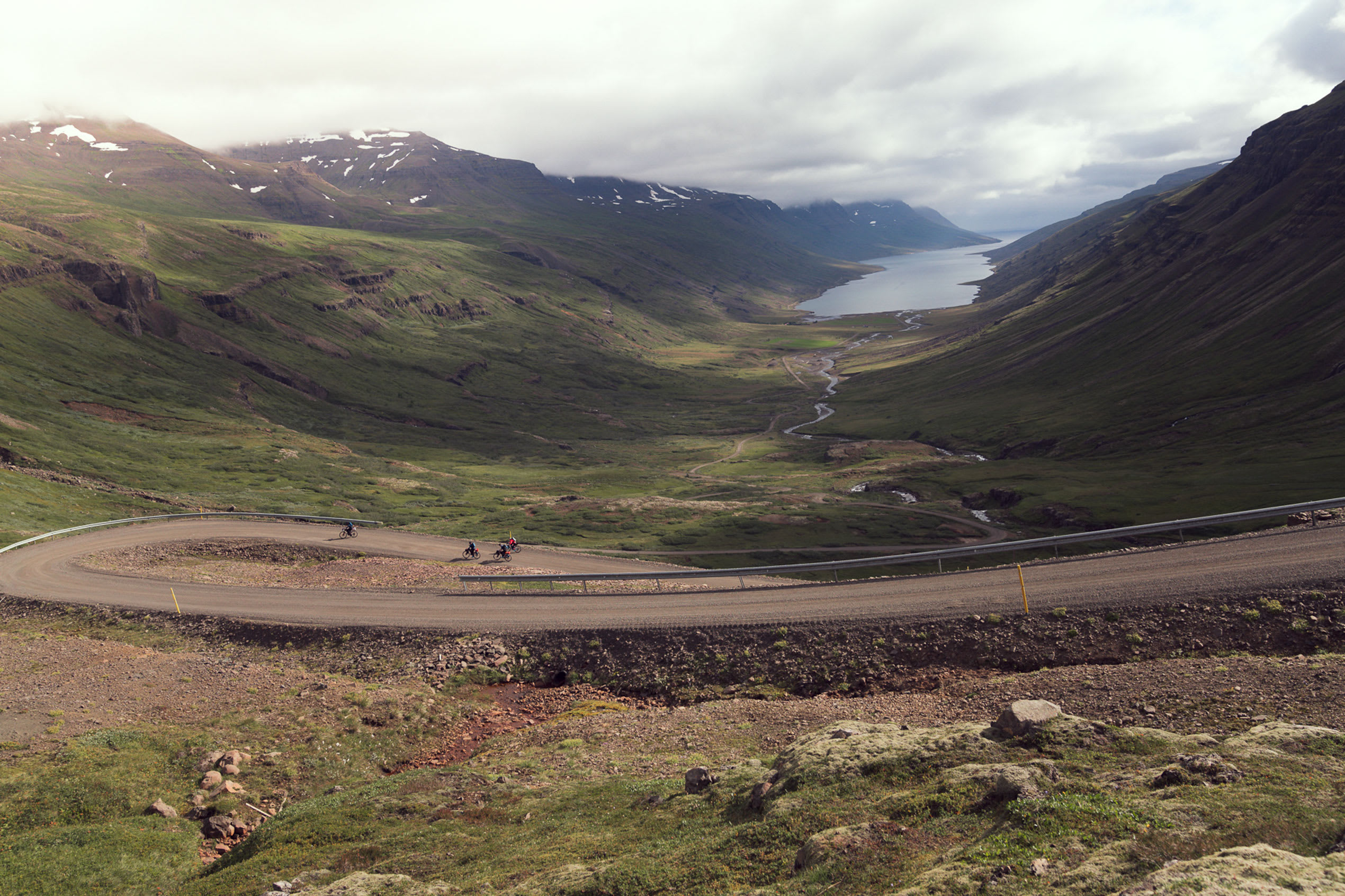 a view of a road weaving down into a fjord in Iceland, with water visible in the far distance